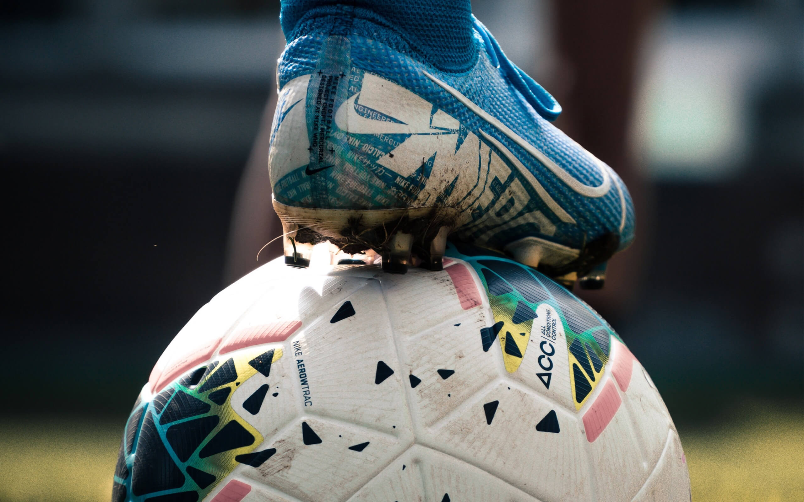 A blue football boot resting on top of a football.