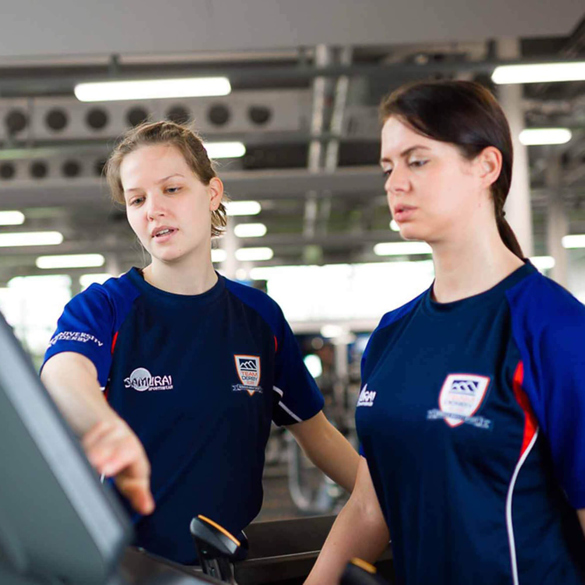 A female student assisting another female student on a running machine.