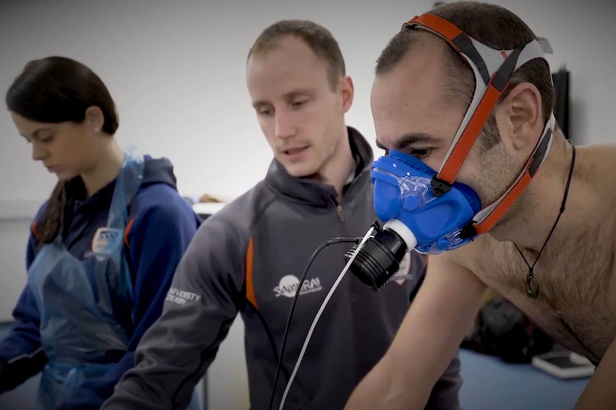 Mark Faghy conducting research in the background, with a man wearing an oxygen mask.
