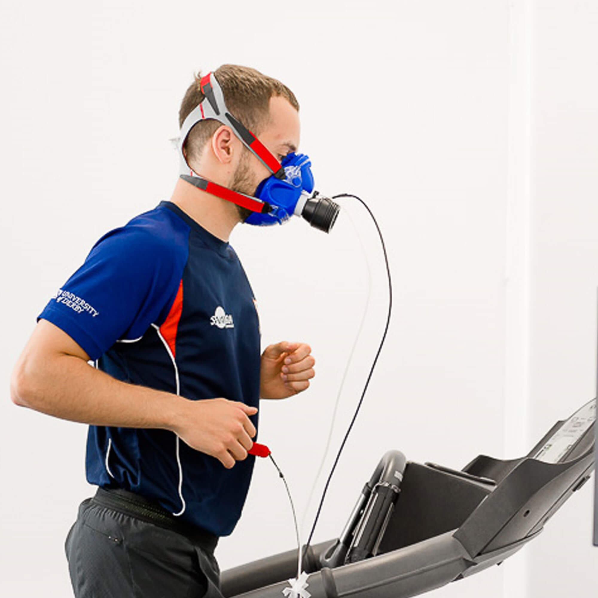 A man running on the treadmill, with monitoring gear on
