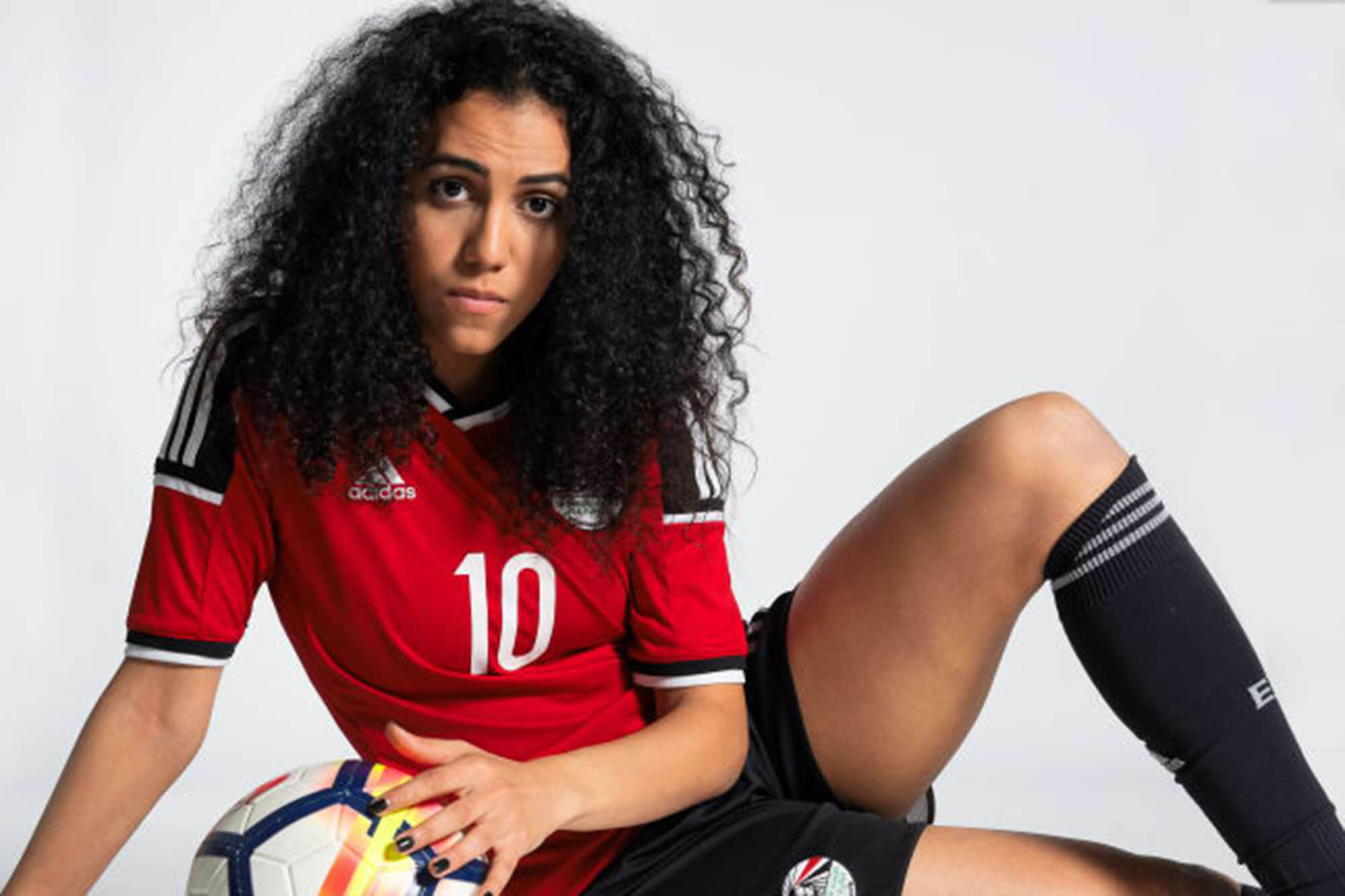 Sarah Essam (Female Egyptian footballer) sat on the floor holding a football looking at the camera