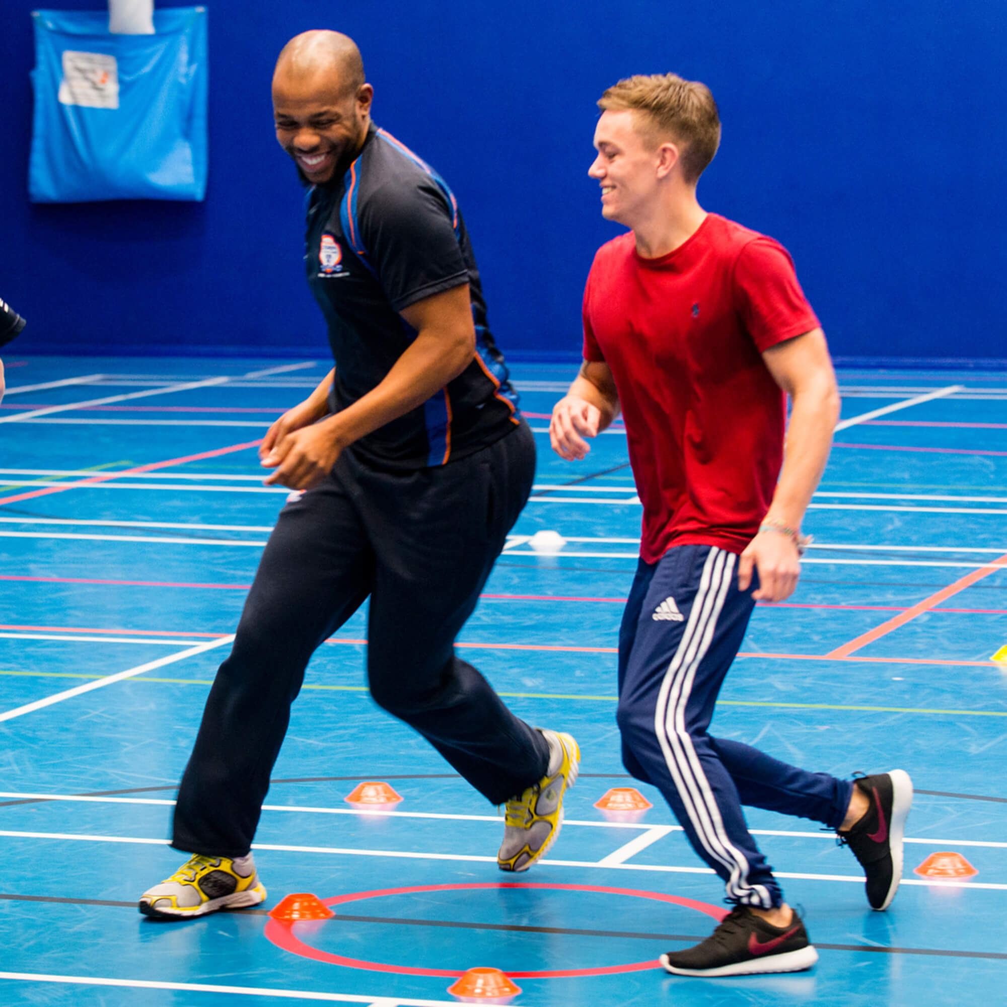 A male academic running in a sports hall with a pupil.