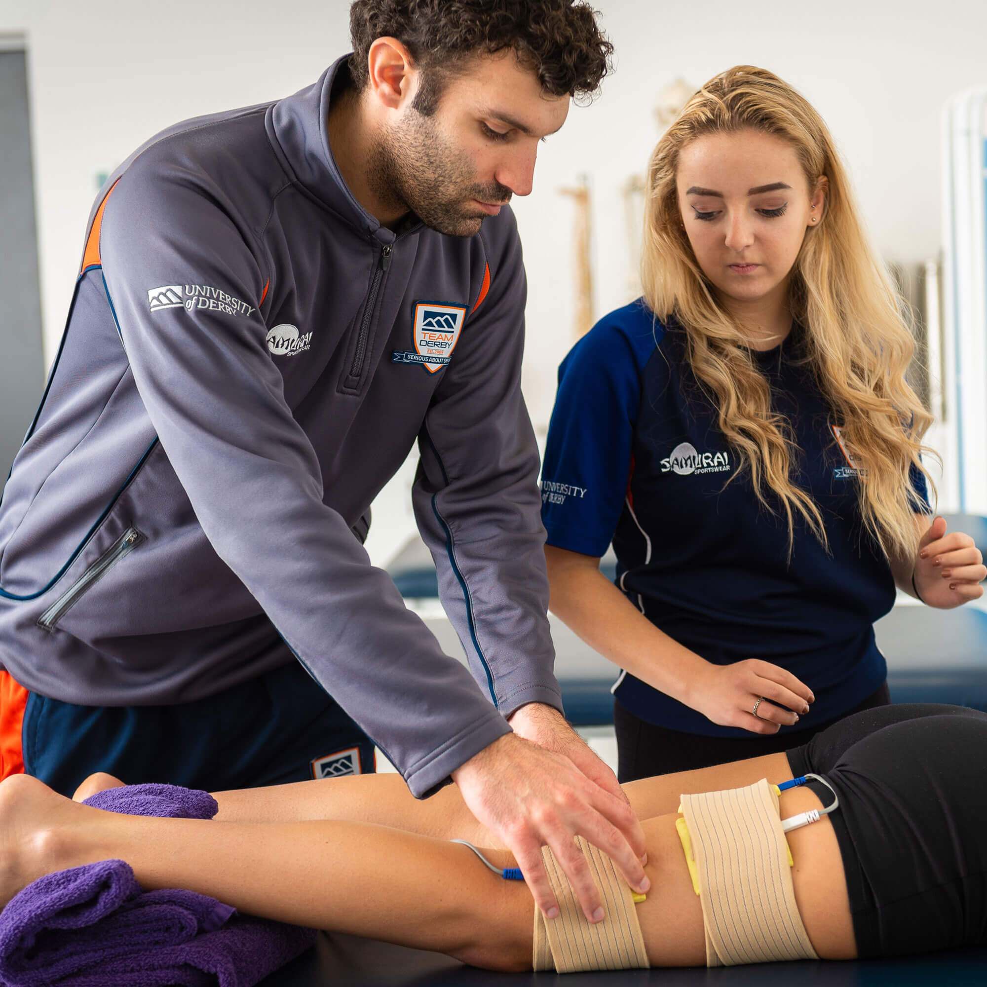 Sports therapy student treating patient with assistance of an academic