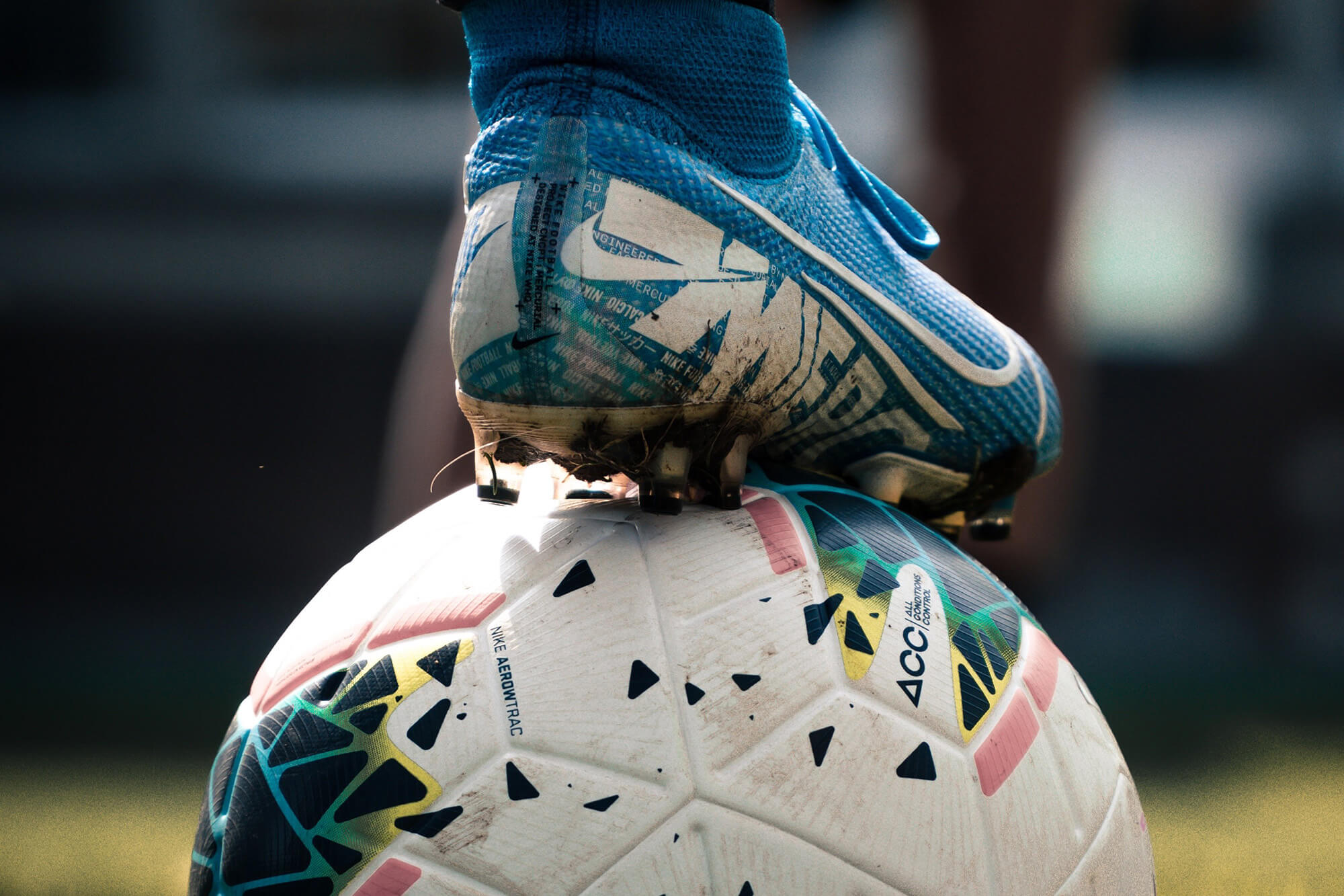 A foot with a football boot resting on top of a football.