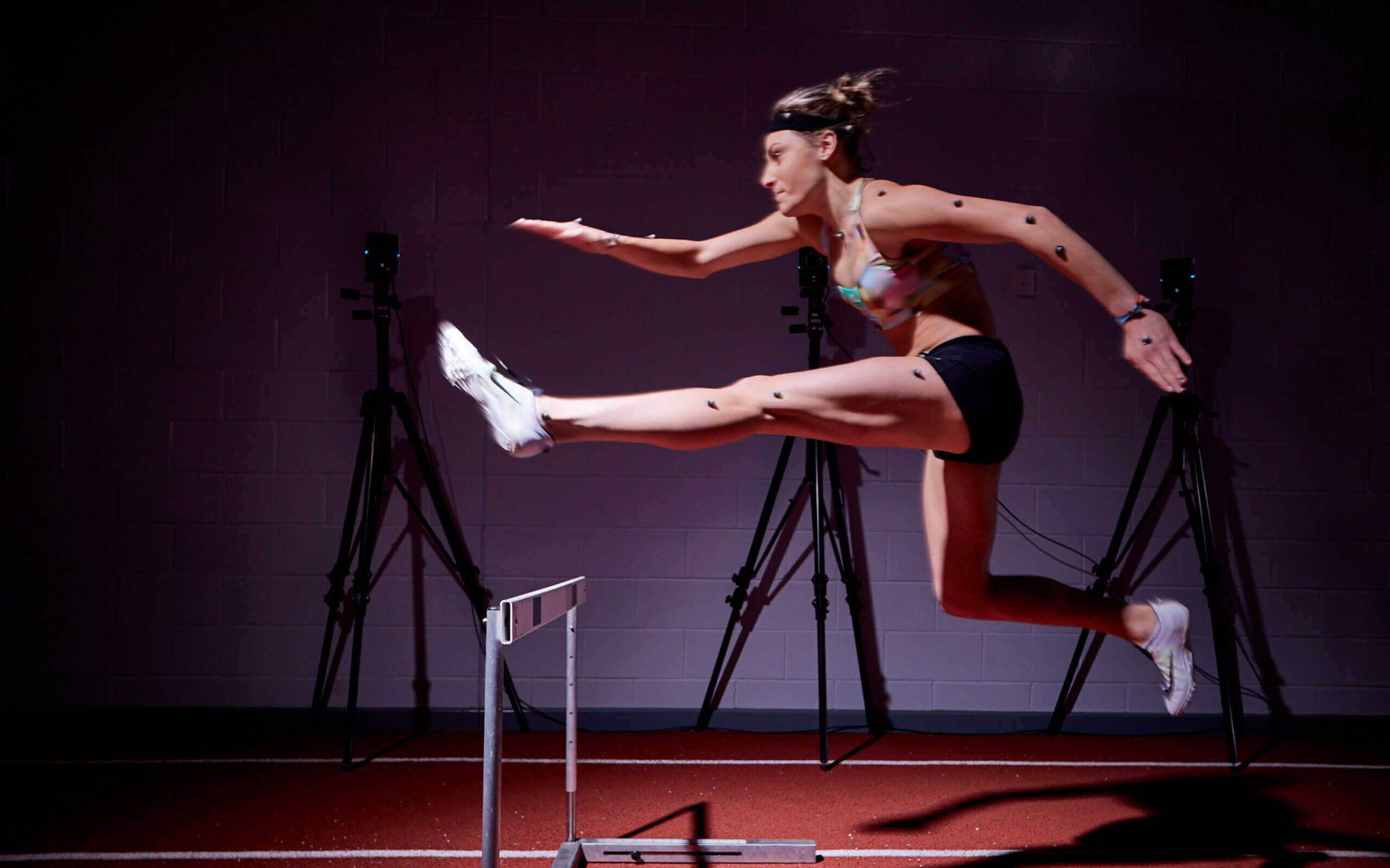 A lady jumping over a hurdle whilst her movements are being monitored