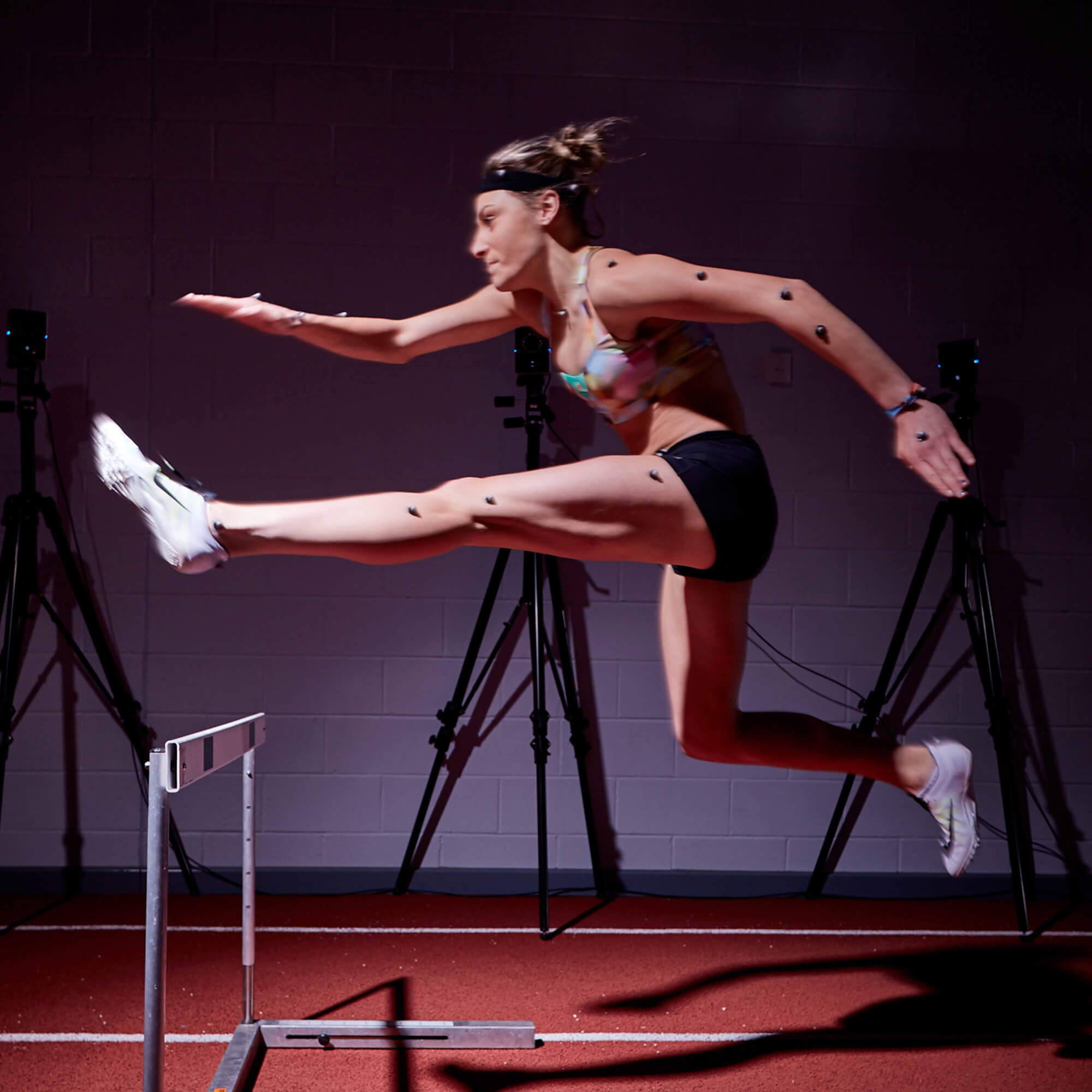 Image of a female hurdler jumping a hurdle with the VICON camera examining her movement