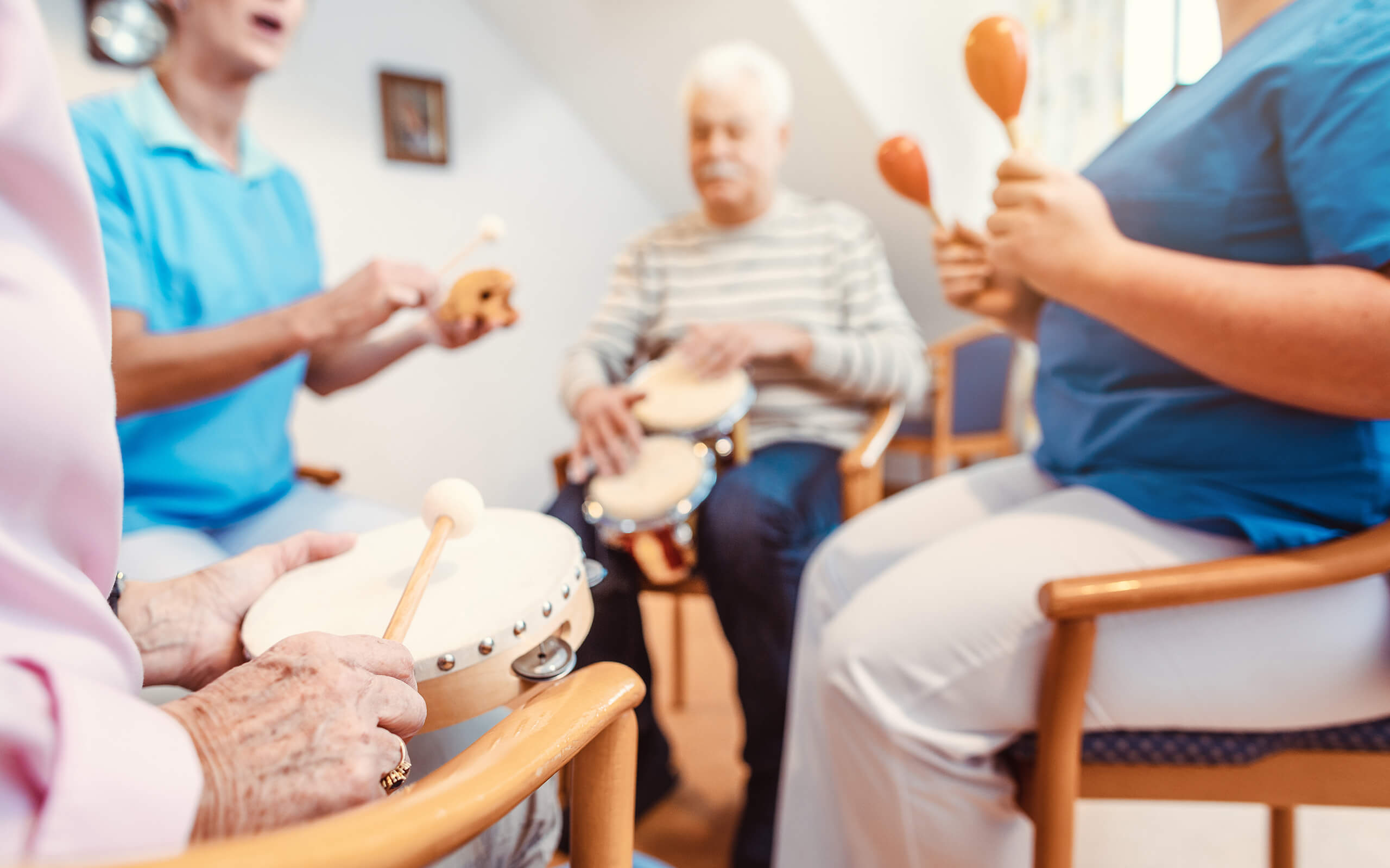 older people in a nursing home sitting down playing simple musical instruments