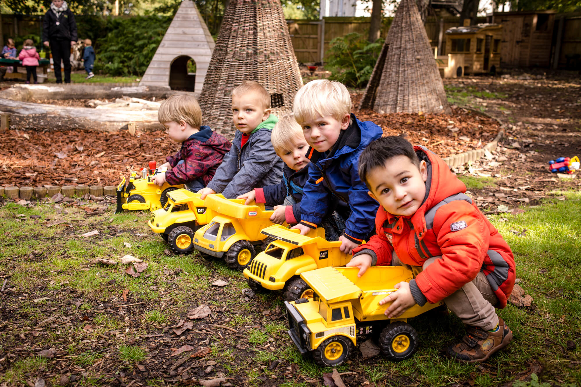 A group of young children in outdoor clothes line up in a forest school environment to have a race with digger toys