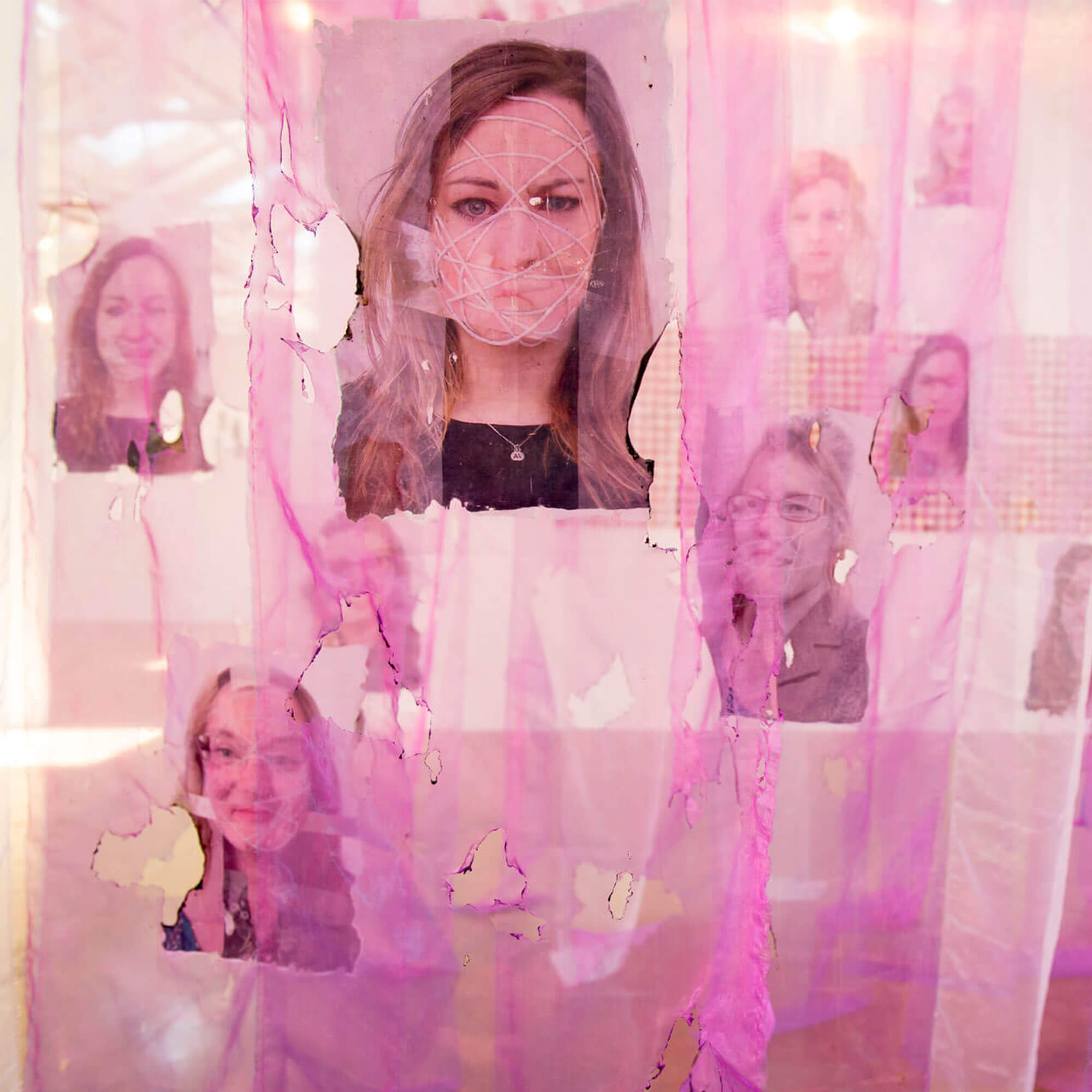 Multiple portrait photos are stuck to a purple fabric that's ripped and hung from a ceiling
