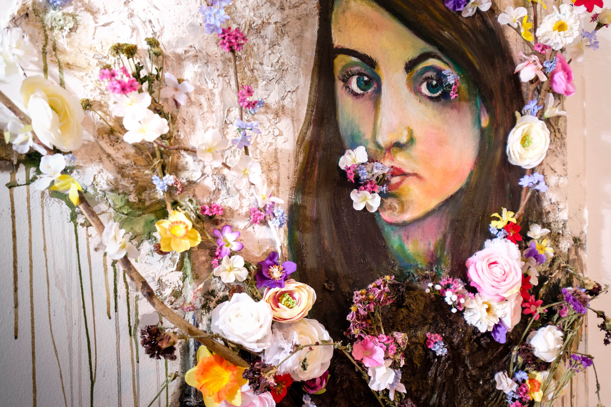 A colourful collage of a painting of a woman with 3d flowers attached