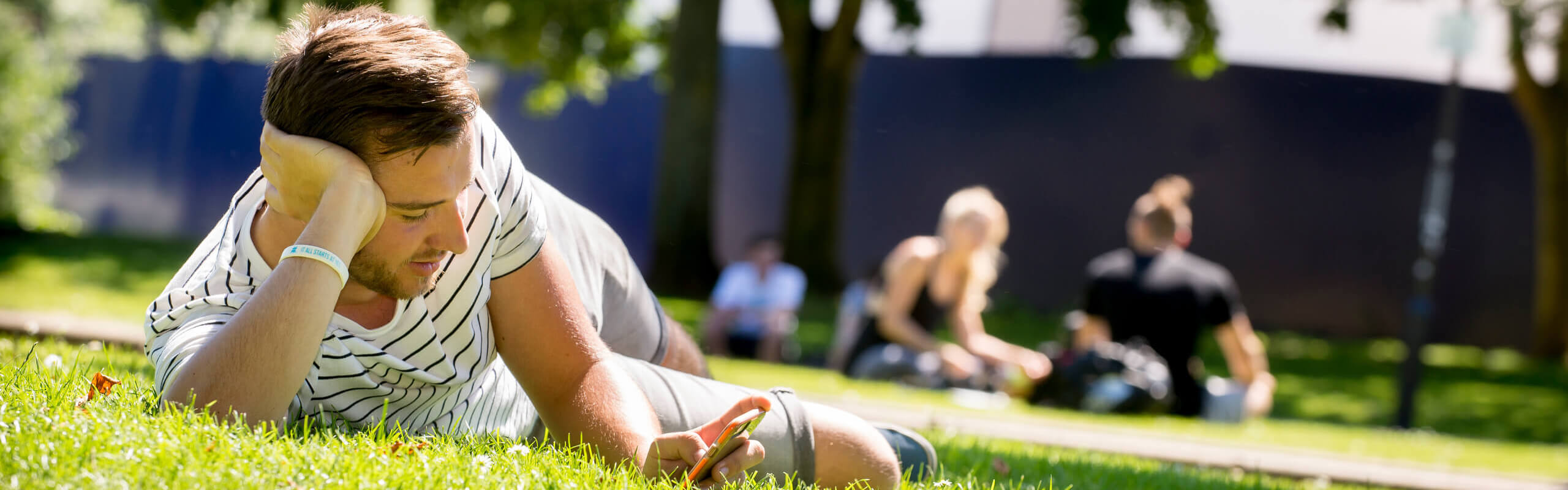 A student lying on grass relaxing