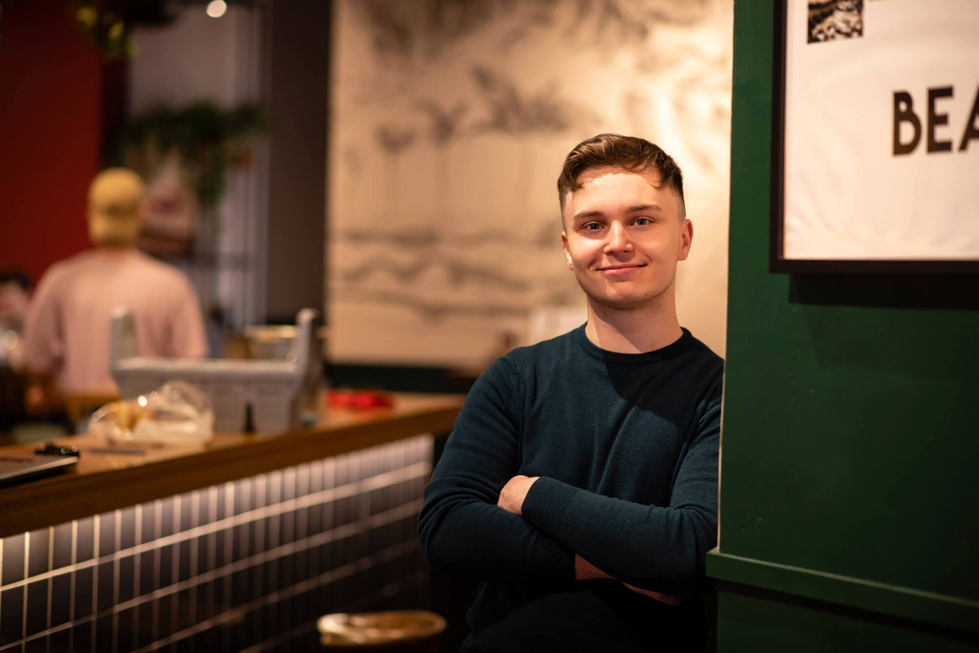 Thomas with his arms crossed, leaning against a wall in a cafe wearing a sweater