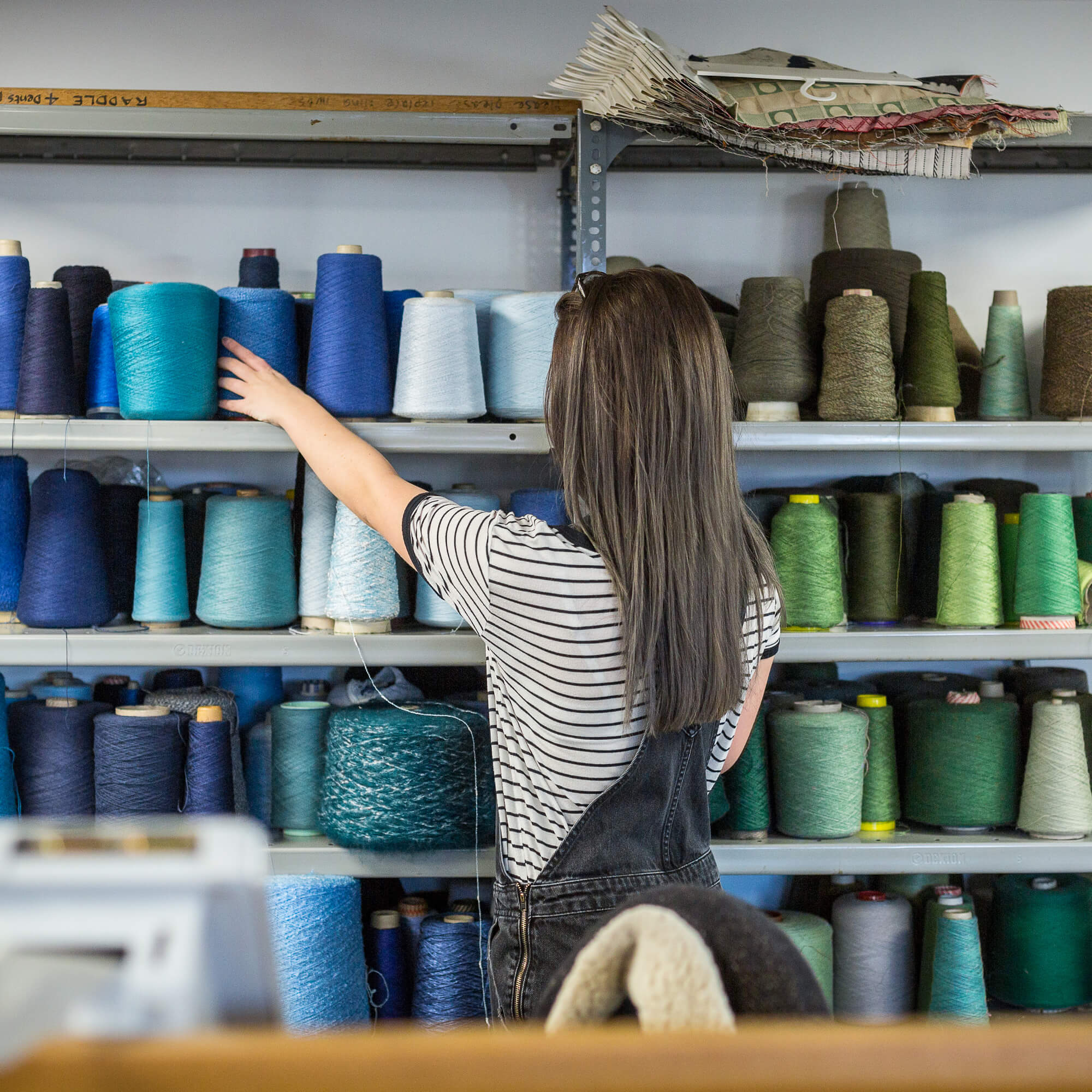 Student in textiles workshop with large spools of thread