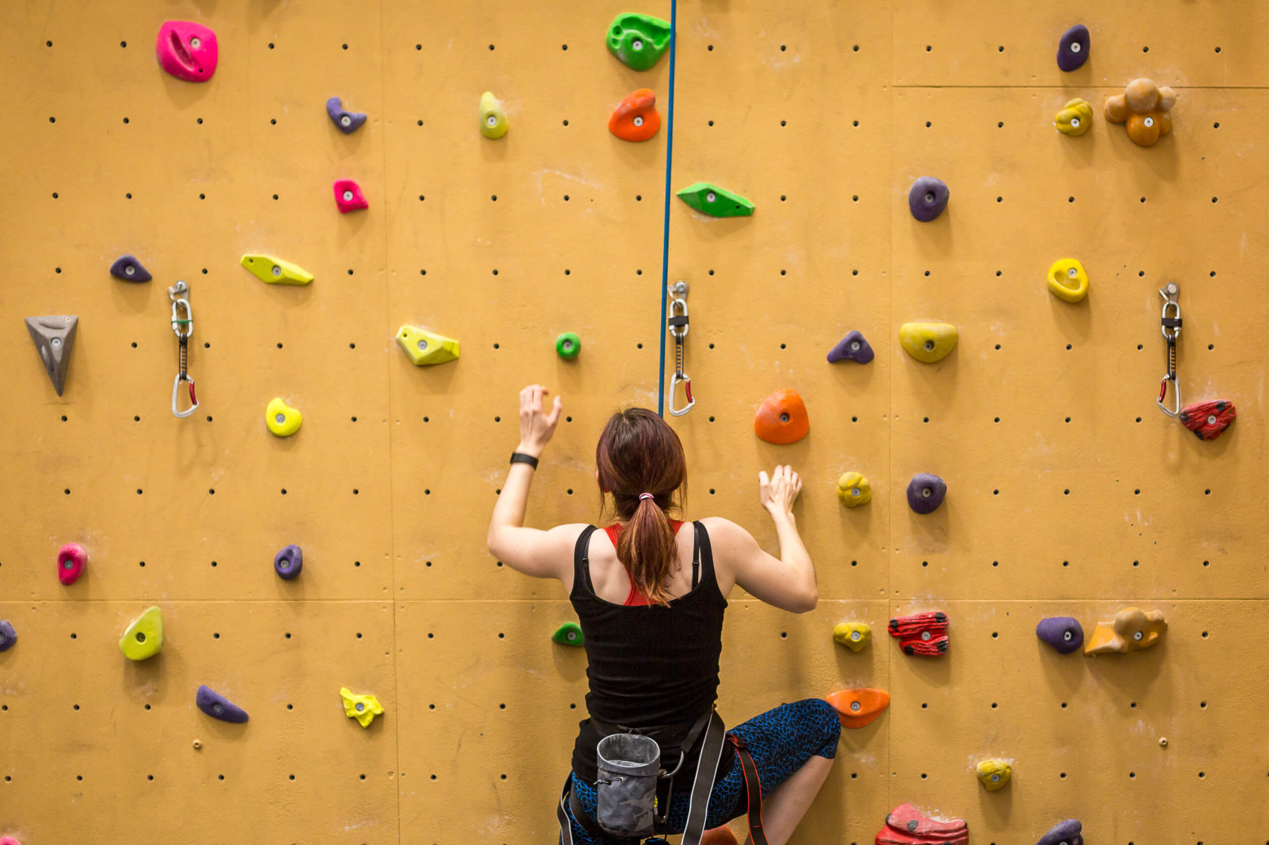 A girl ascending a climbing wall