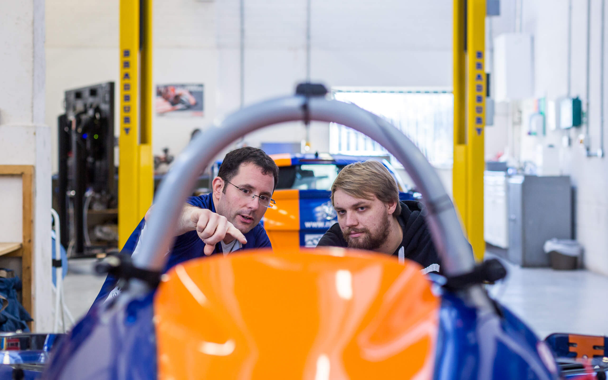 Student and academic looking at orange and blue model car for Motorsport engineering