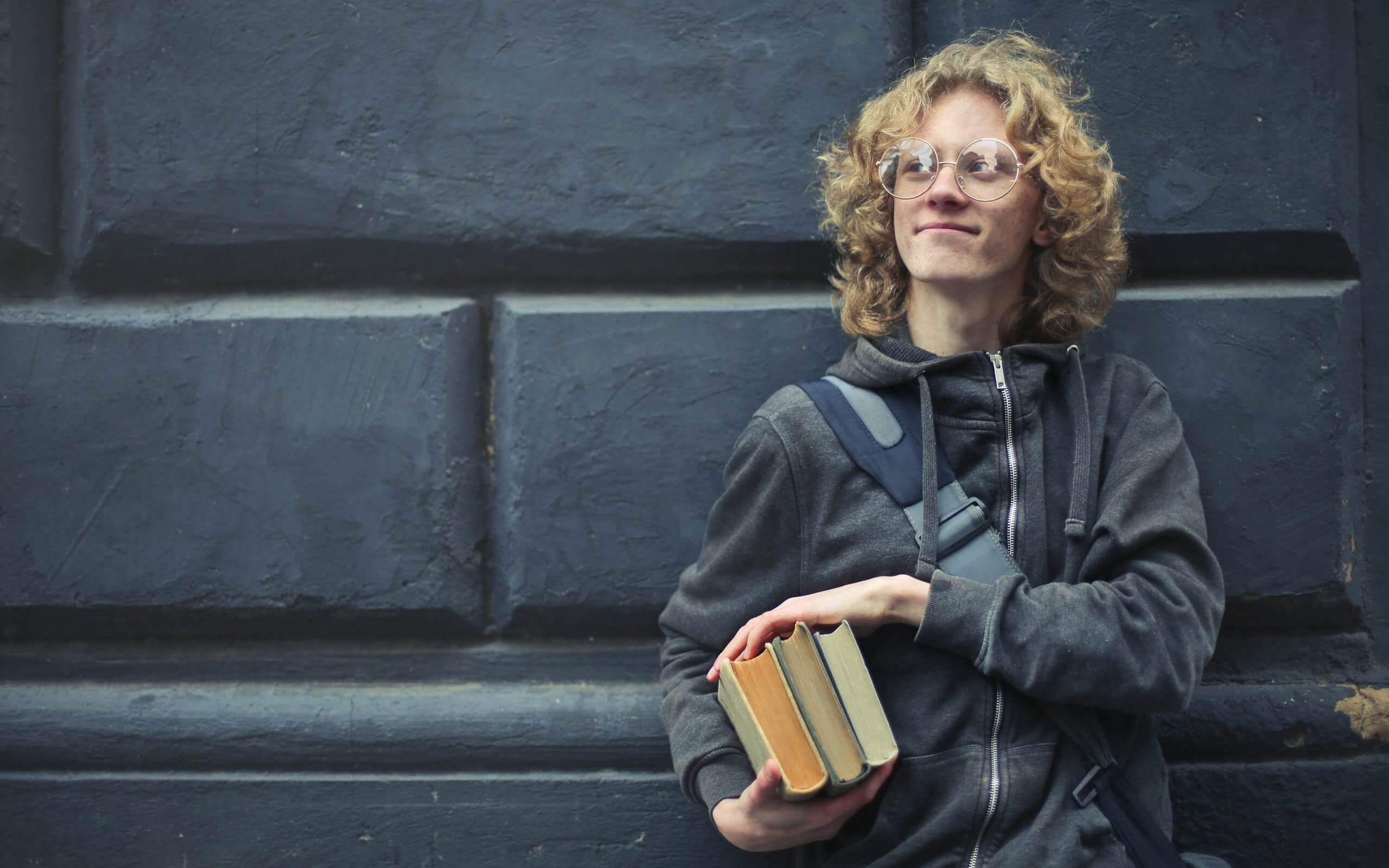 Young man leaning against a wall holding books