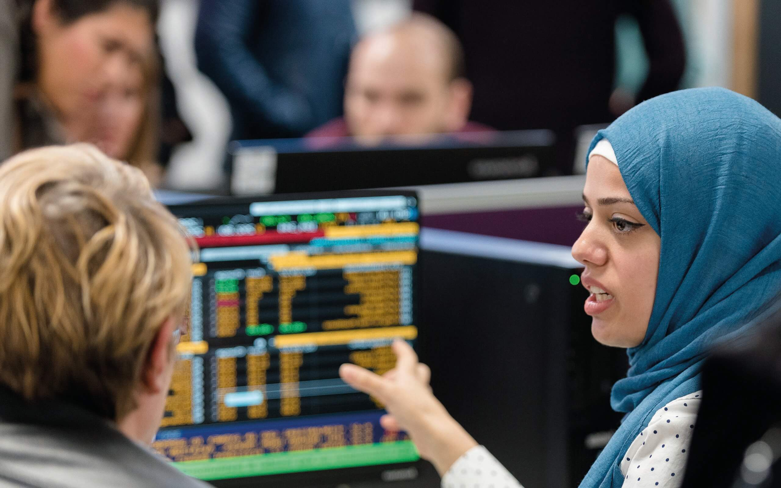 two ladies discussing accounting in front of stock market computers