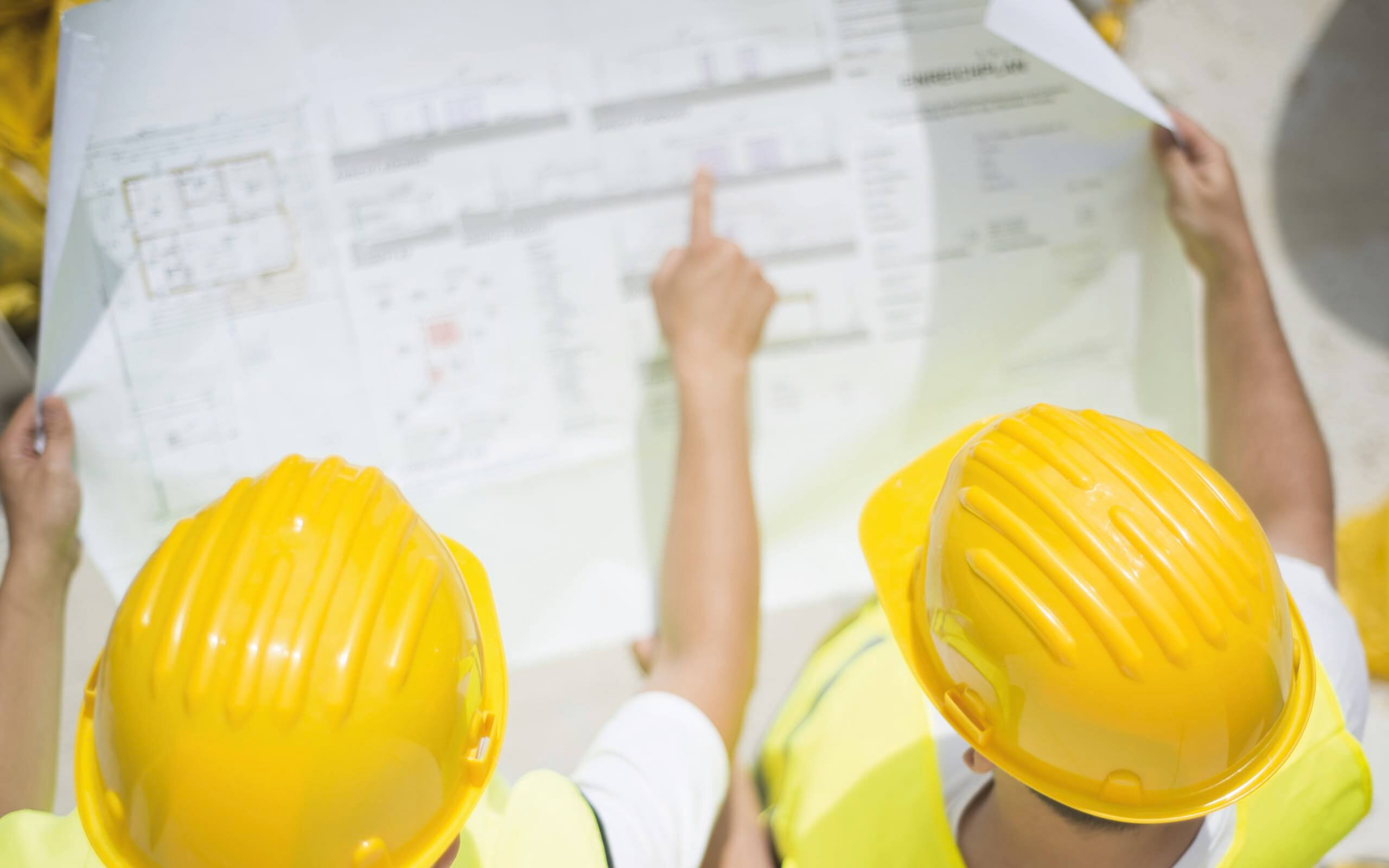 two construction engineers review site blueprints