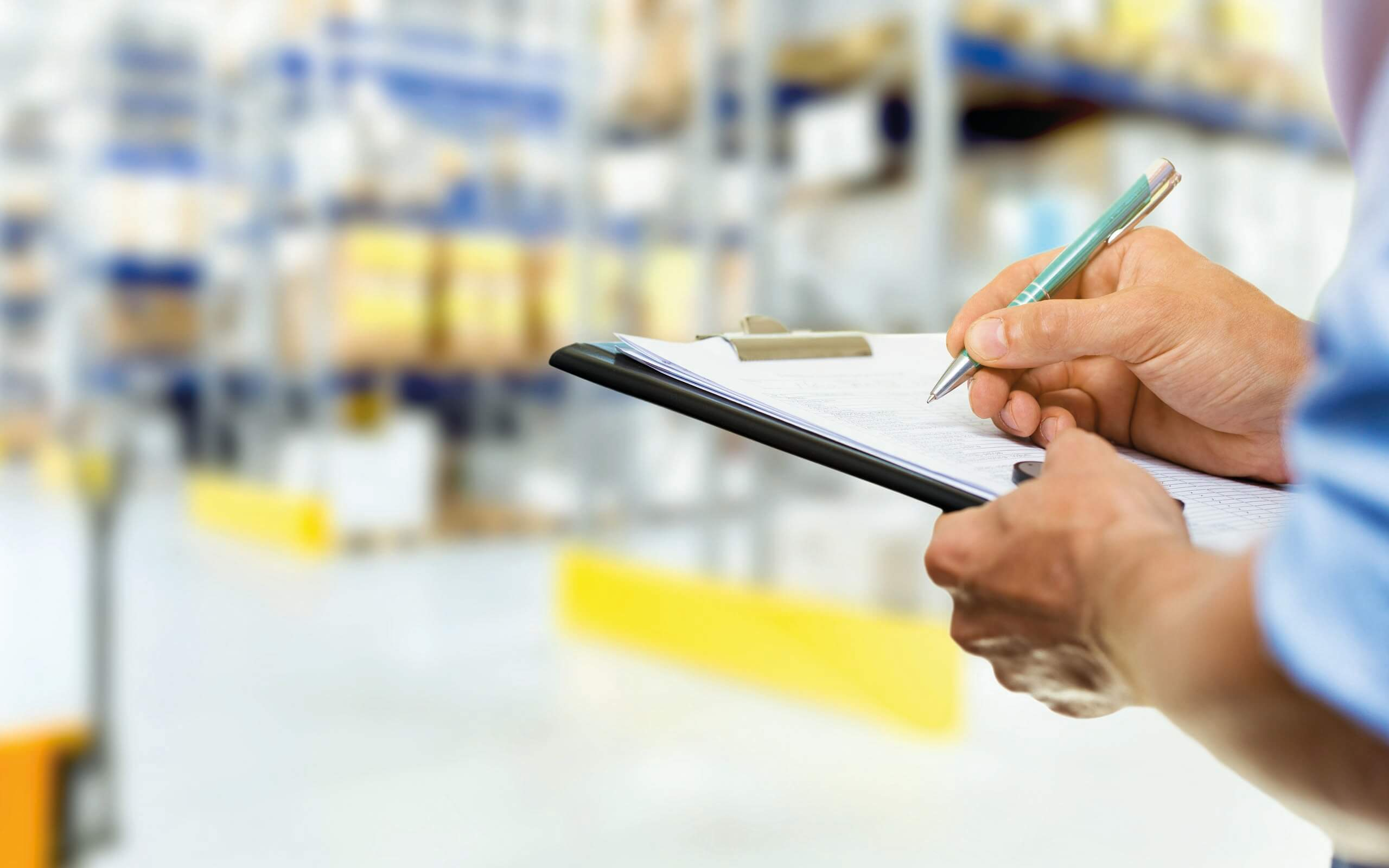 Warehouse manager checks stock and safety in large warehouse