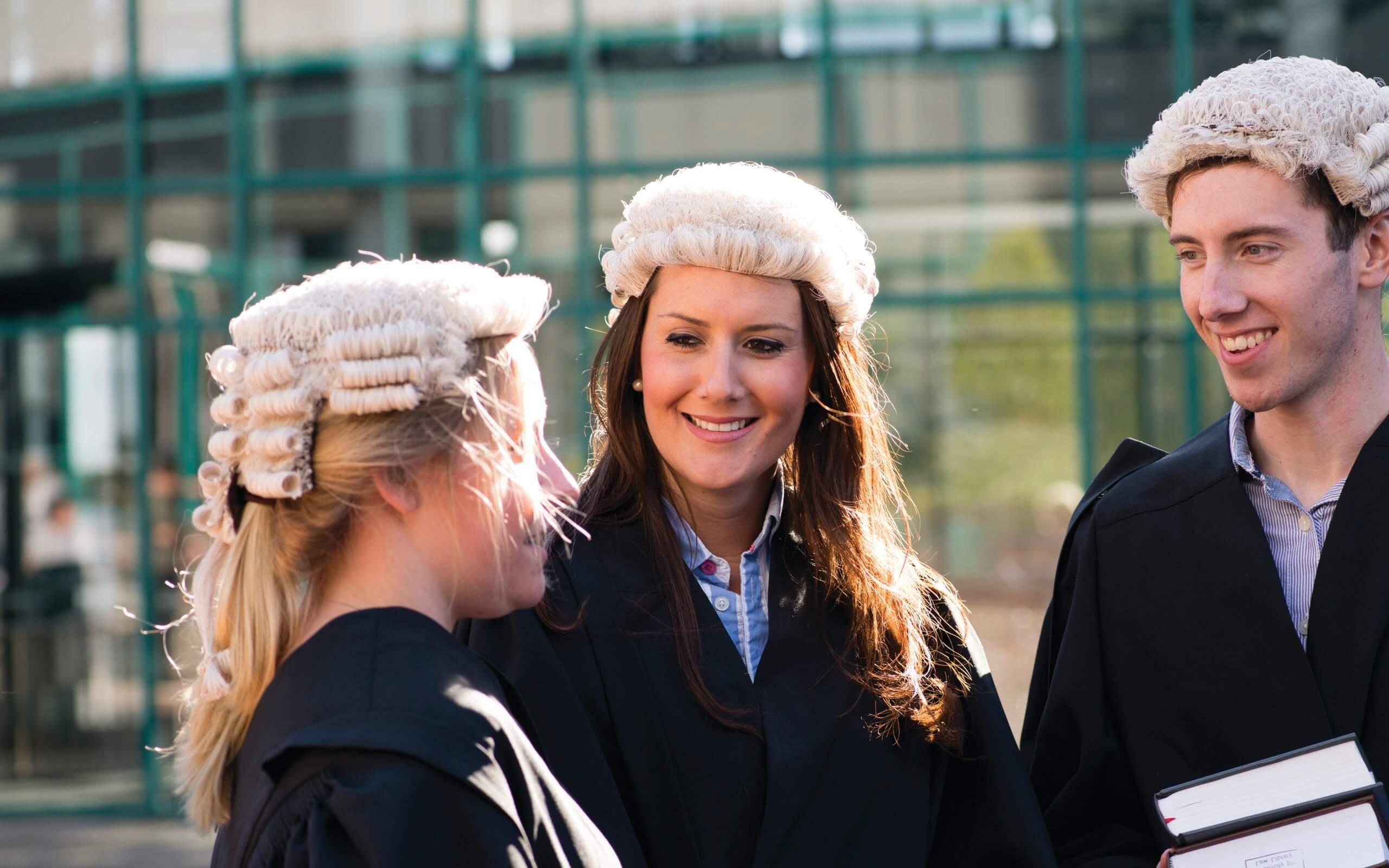 3 law students in legal court dress with legal books