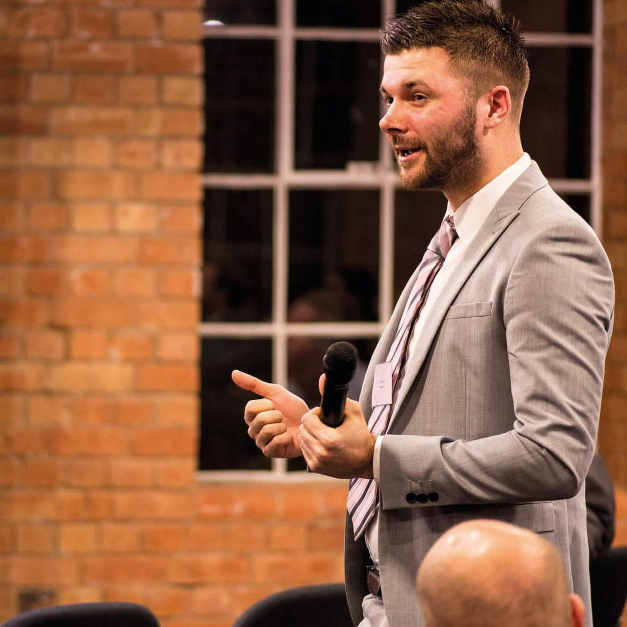 man delivers bsuiness presentation in front of audience