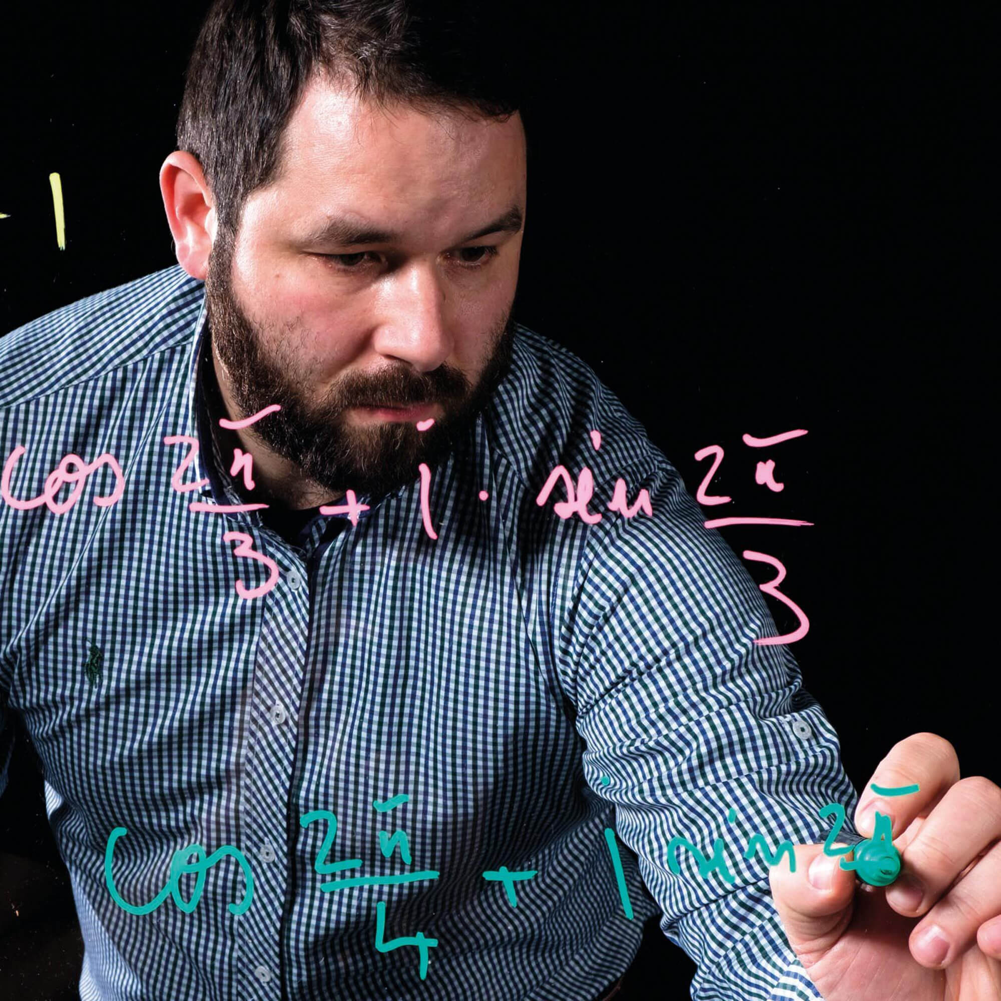 Man writing maths equations on glass screen