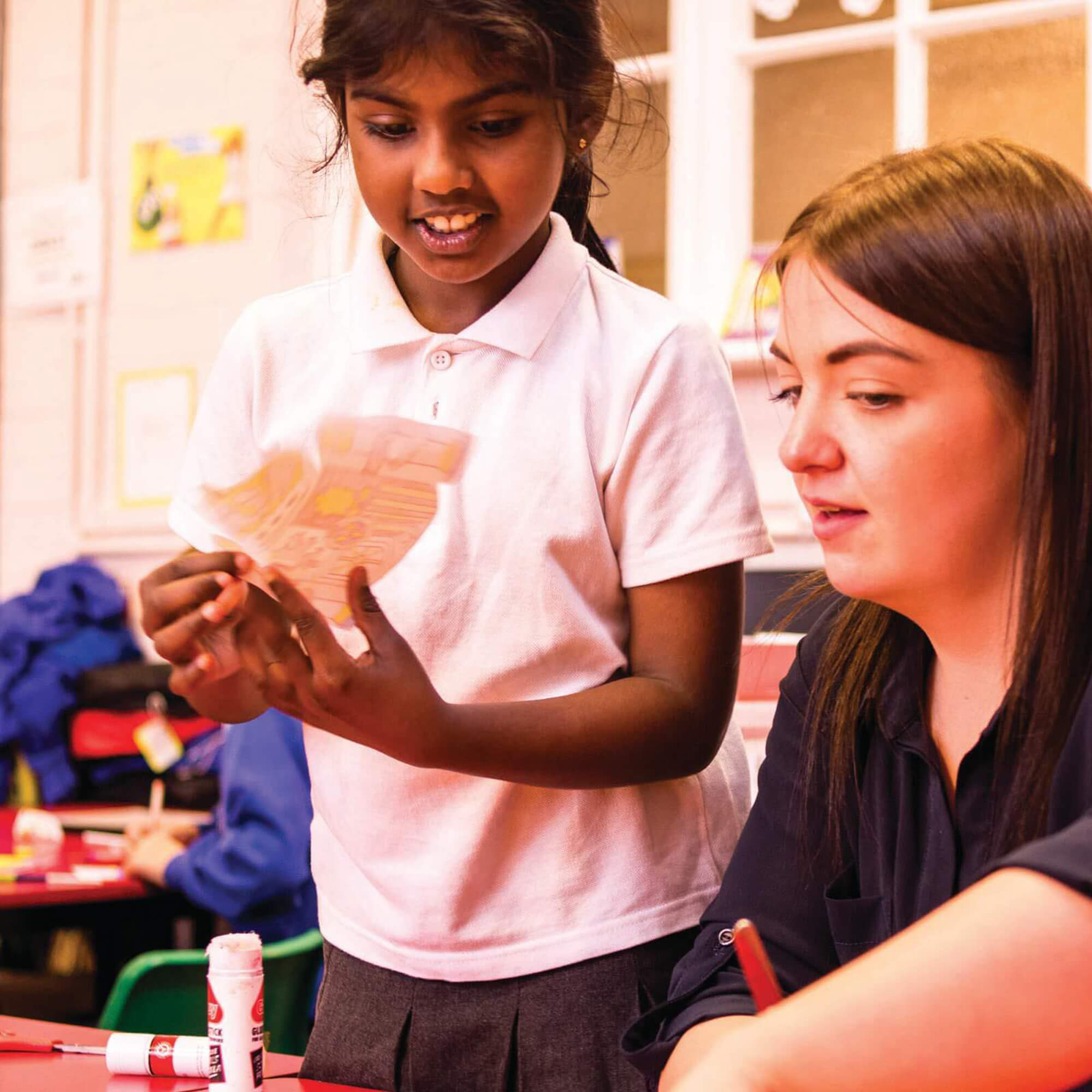 Teacher with primary school pupil working on an art project
