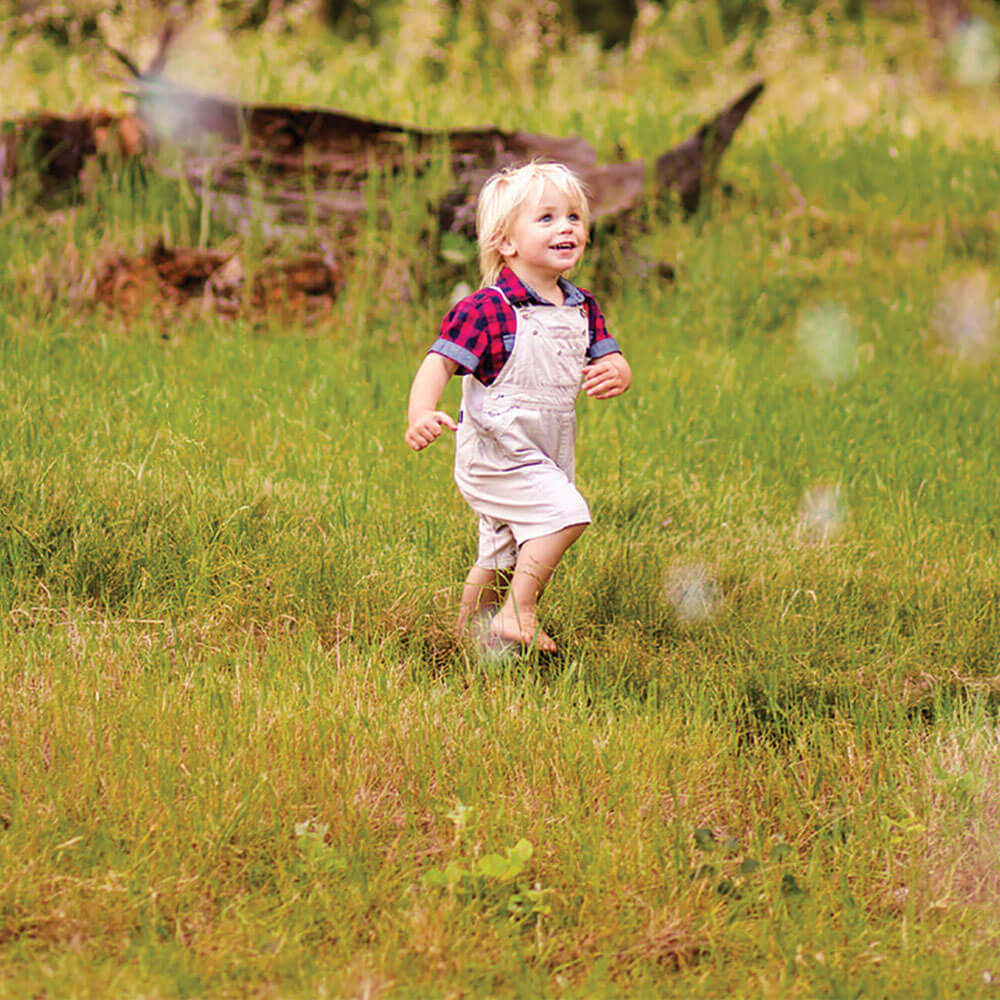 Young child having fun running through a field during Teacher training course