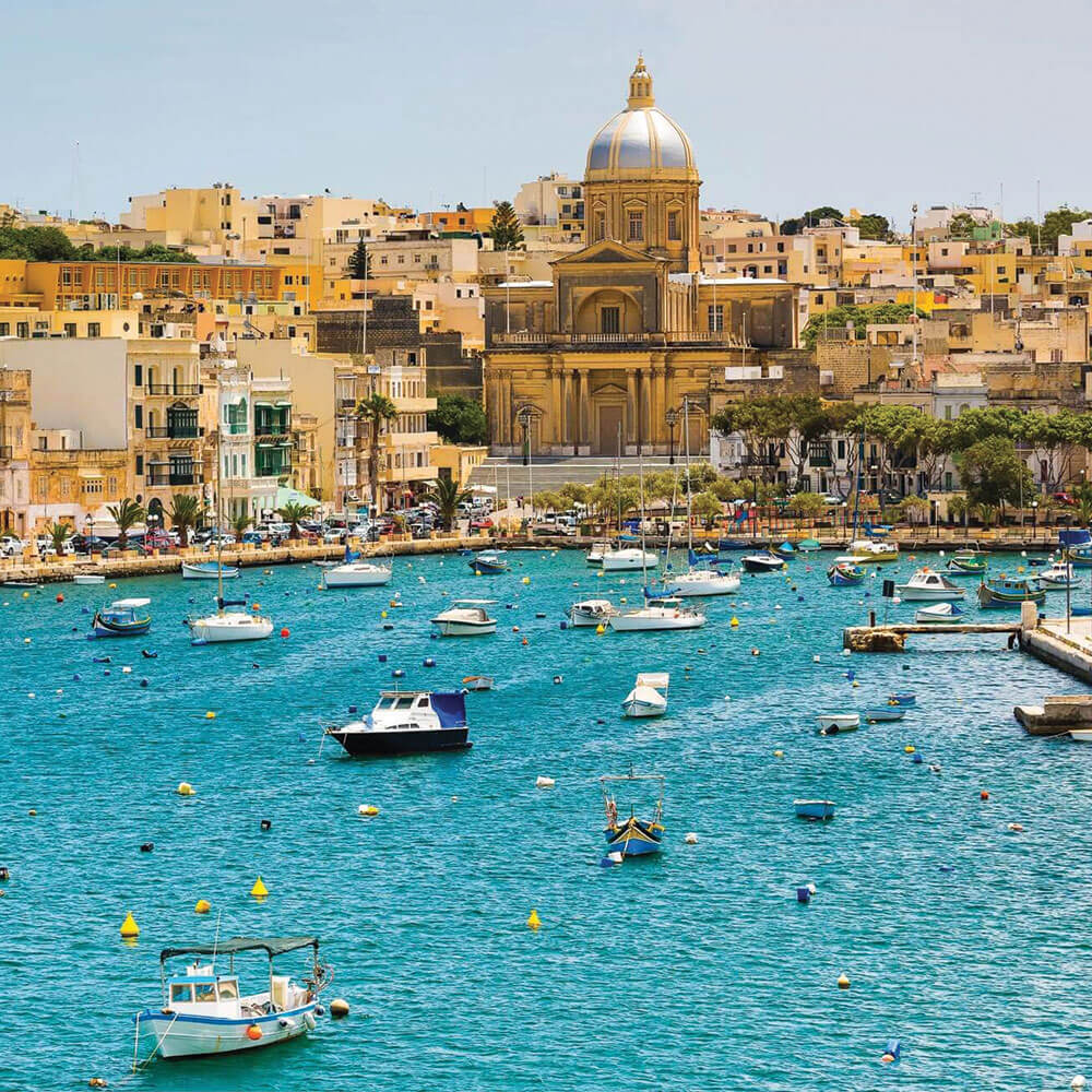 Photo of Malta with sandy coloured buildings with many small boats on blue water for Tourism Management course