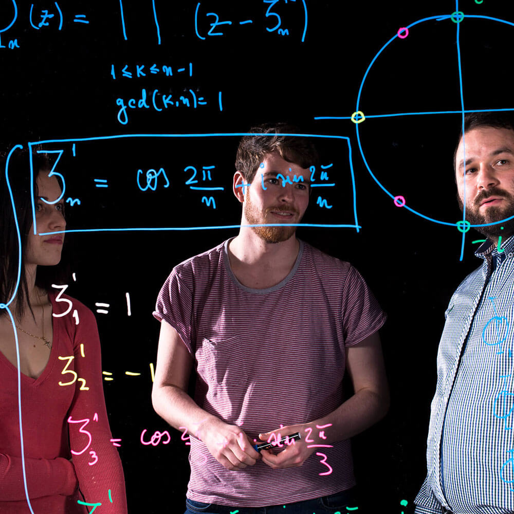 Maths students in front of a board with maths equations during Mathematics courses