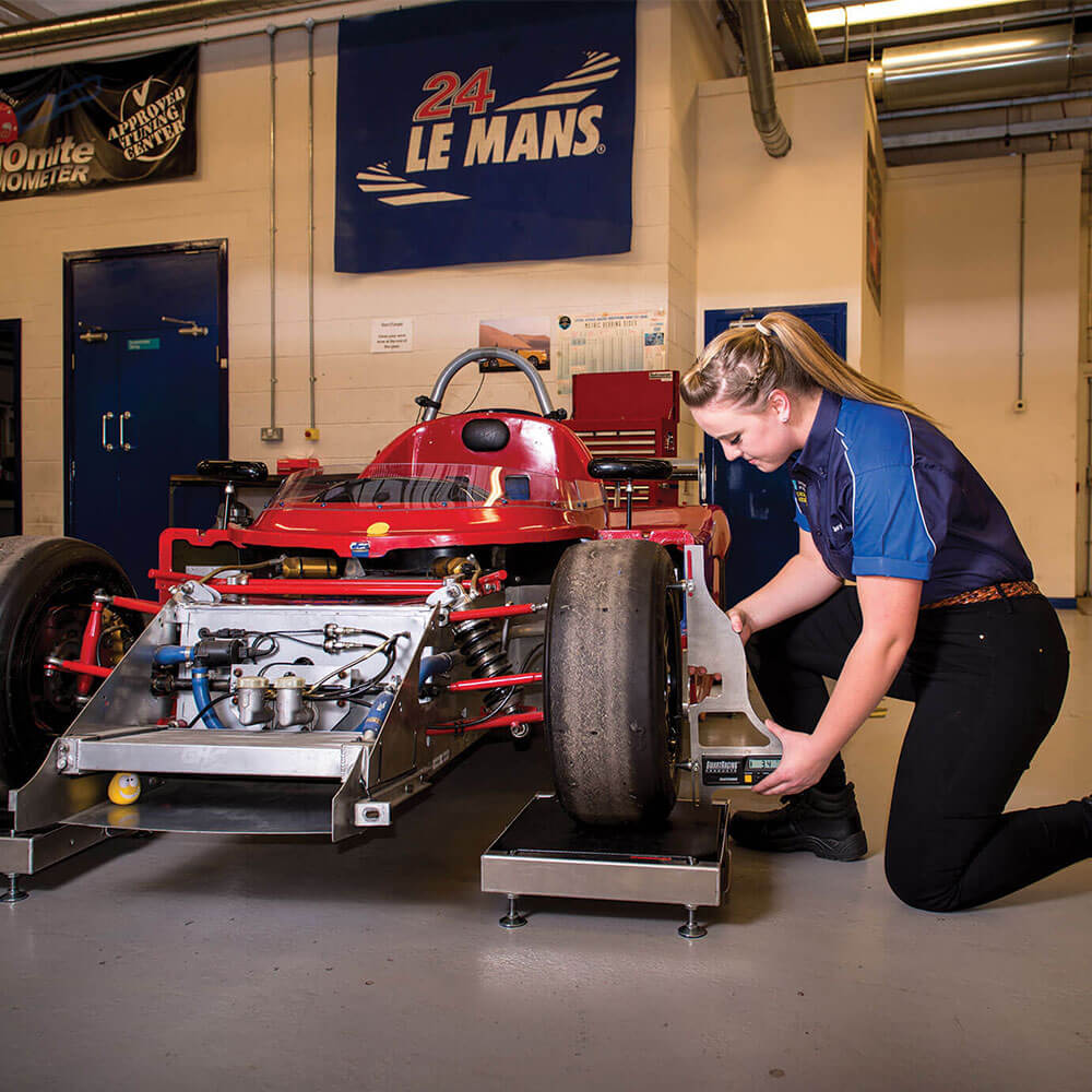 Student measuring an experimental sports car tyre during Motorsport engineering course