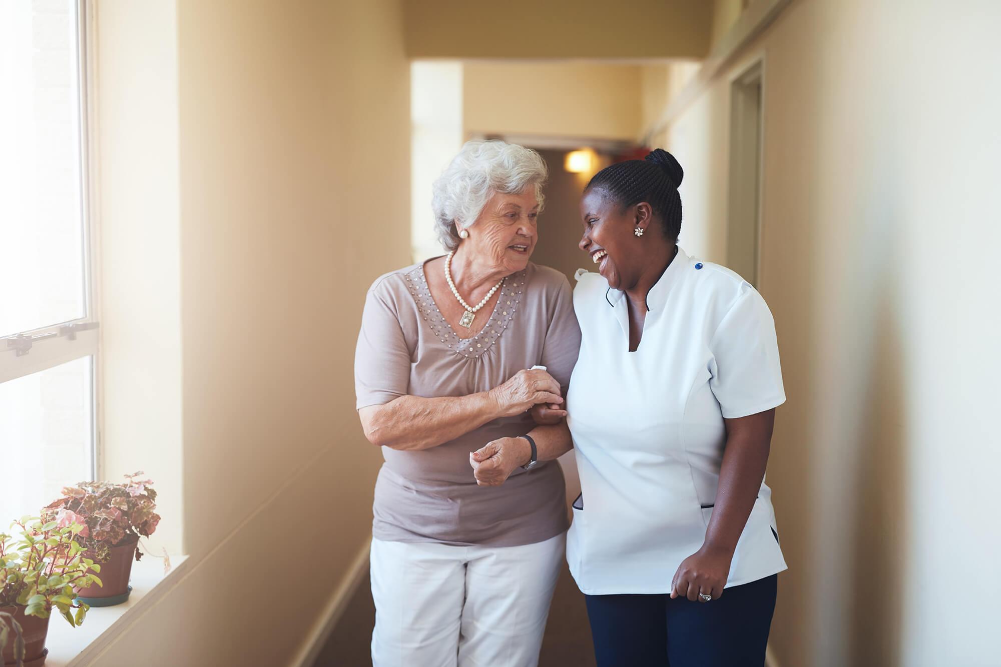 Female nurse walking down a corridor with older lady