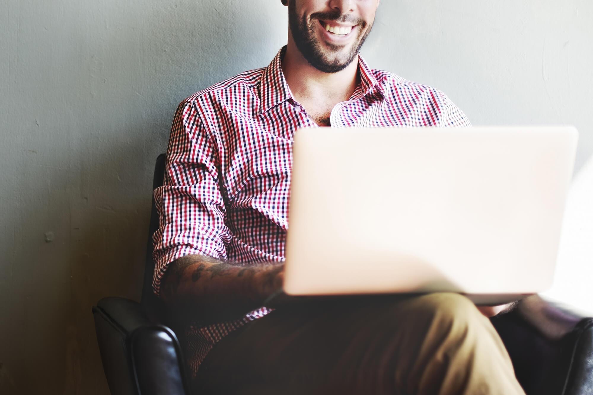 Man sat with laptop on lap smiling