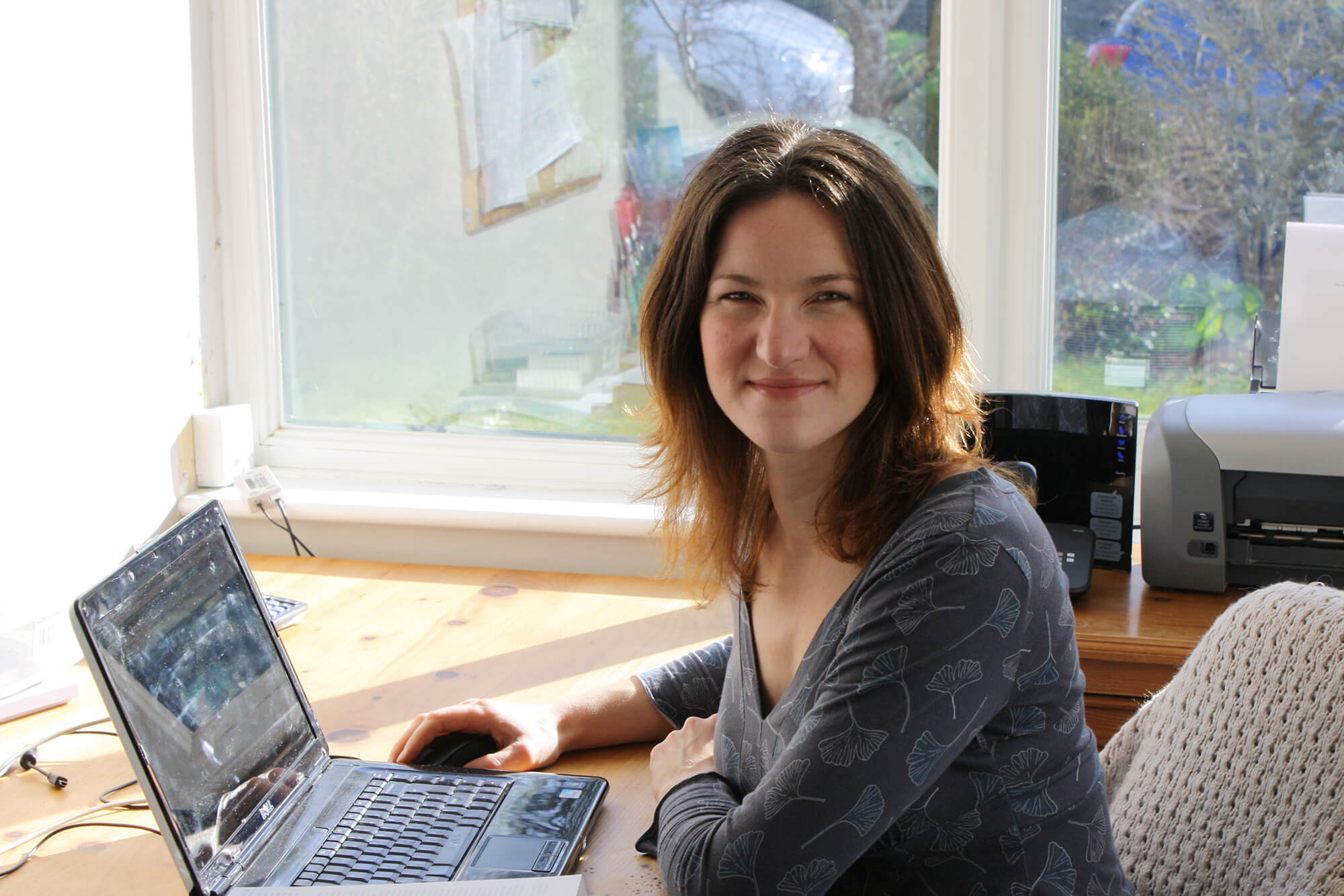 Joy Rickard working at her laptop