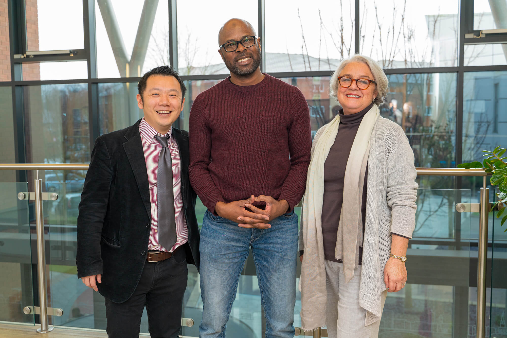 Online student Mo Aledeh standing smiling with academics Yasuhiro Kotera and Christine Rhodes