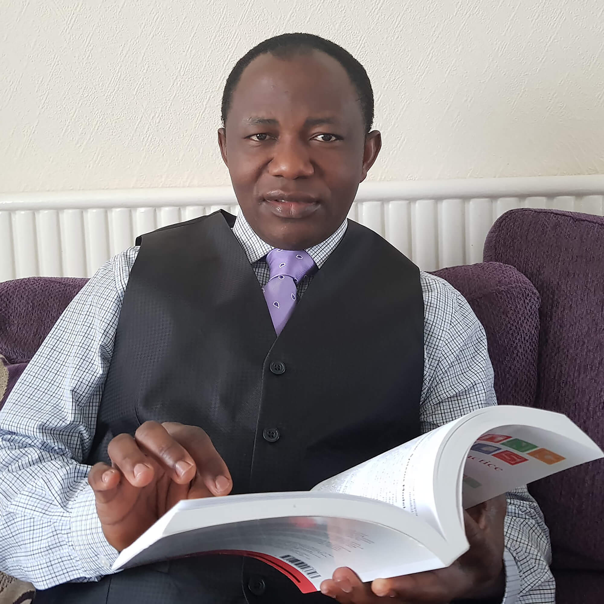 Stephen Sadiku sat reading a book