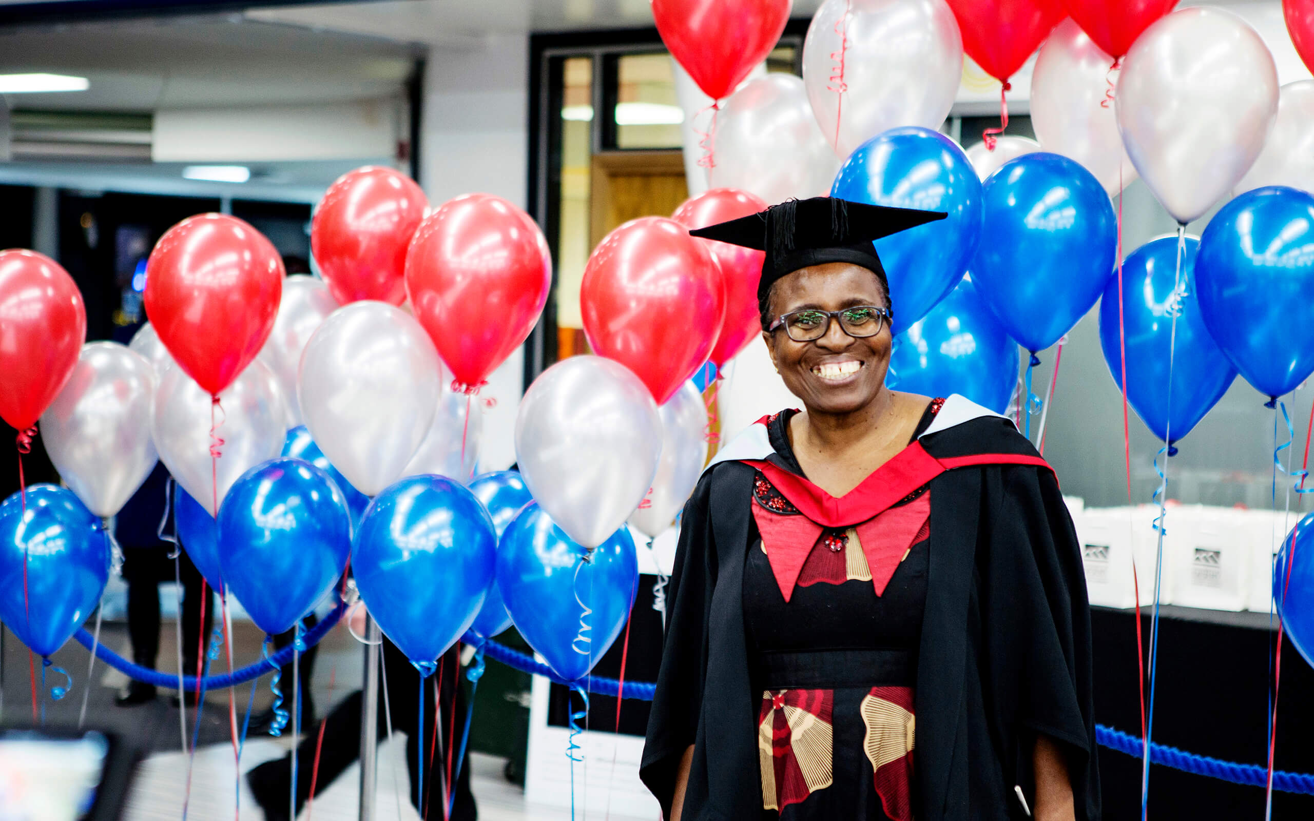 Online student Thobekile Ncube stood at her graduation reception in front of balloons.