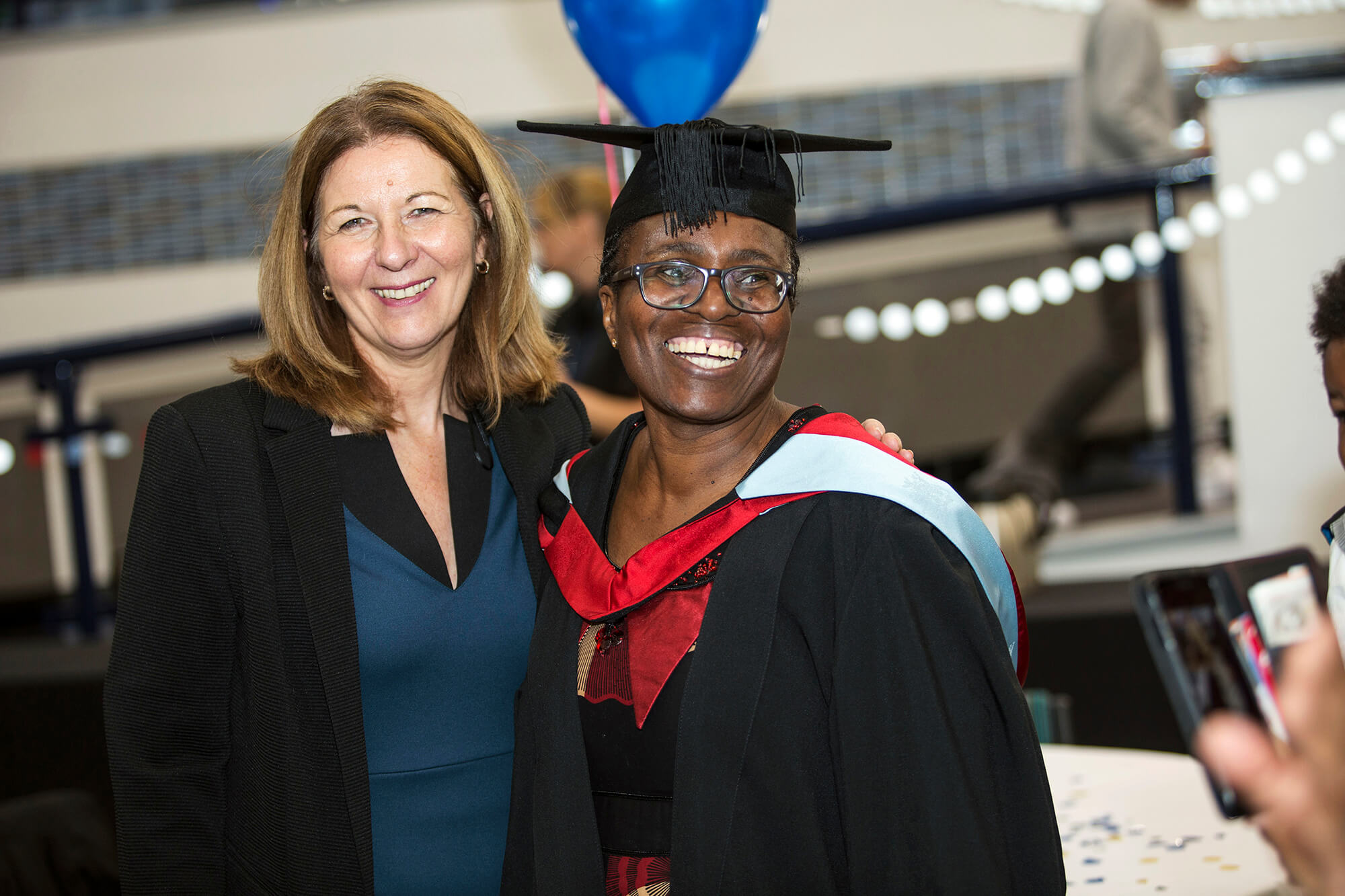 Online student Thobekile Ncube stood with Julie Stone at her graduation reception