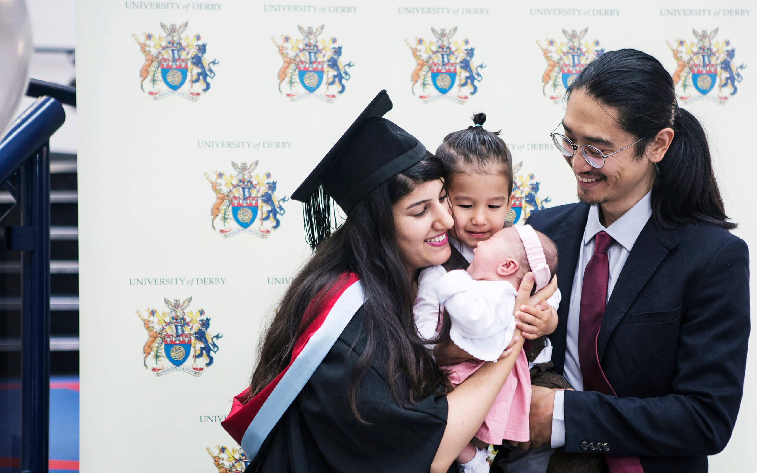 Student Tyra Johl in her graduation gown holding her two children next to her husband