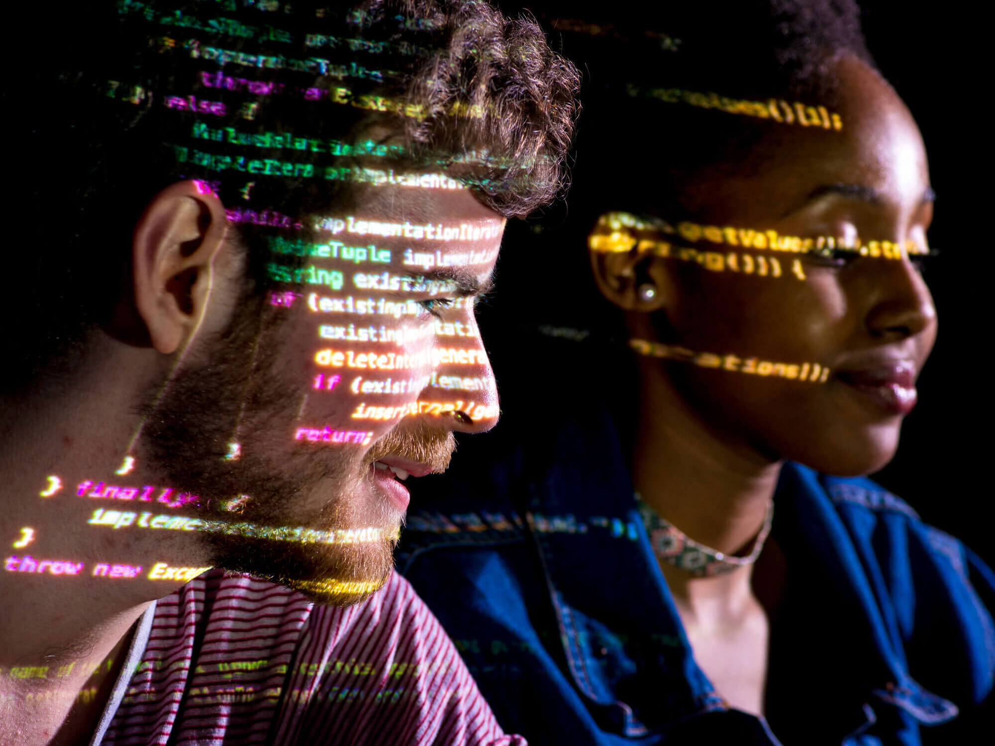 Students with reflection of computing code over their faces