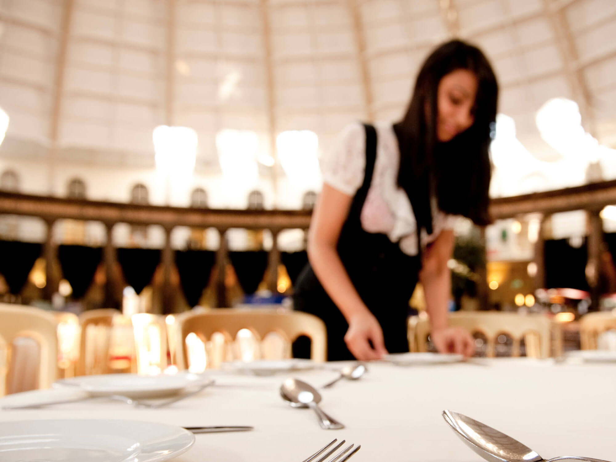 Hospitality student setting a table at an event