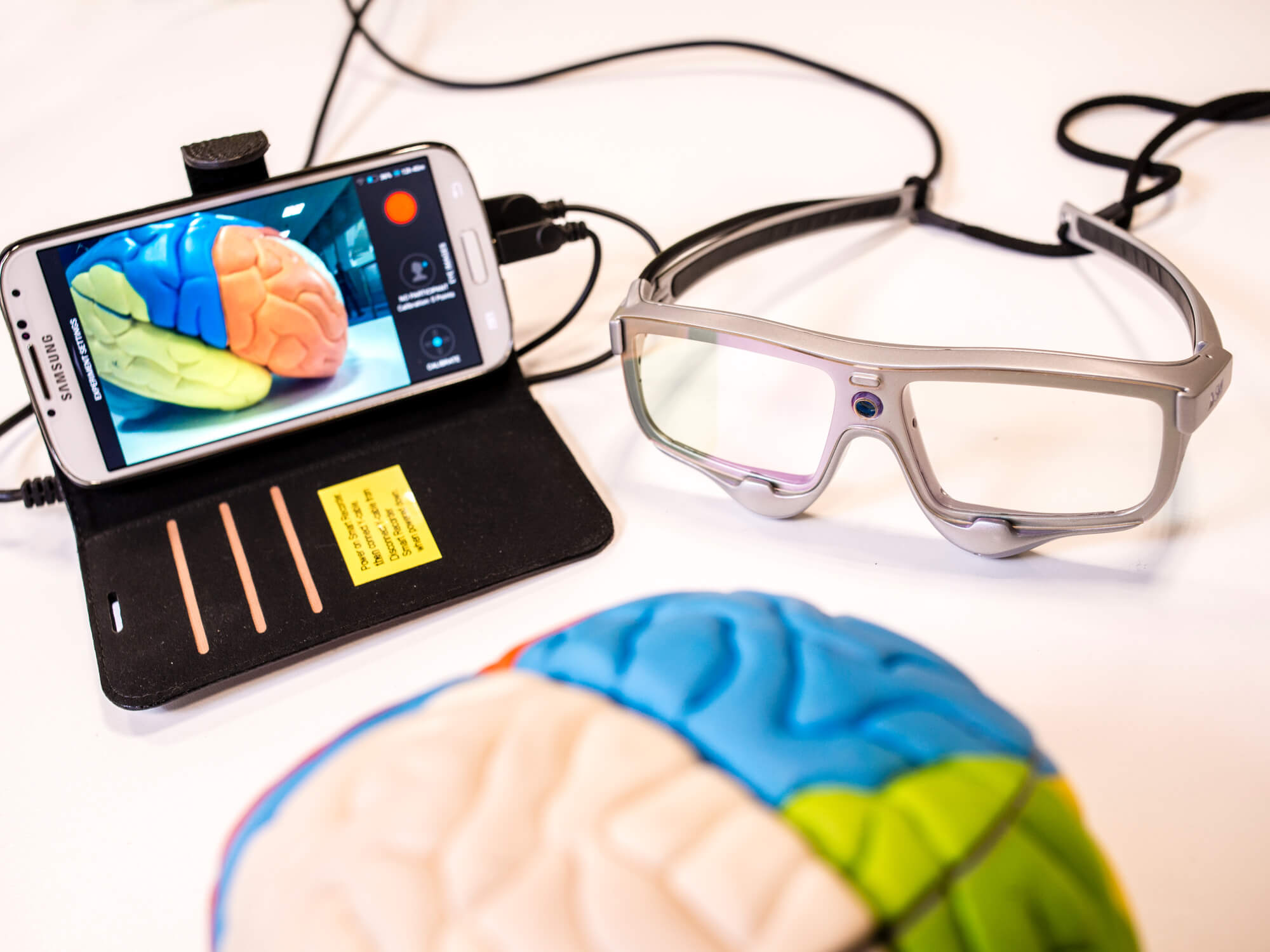 Mobile phone connected to glasses with camera recording a model brain