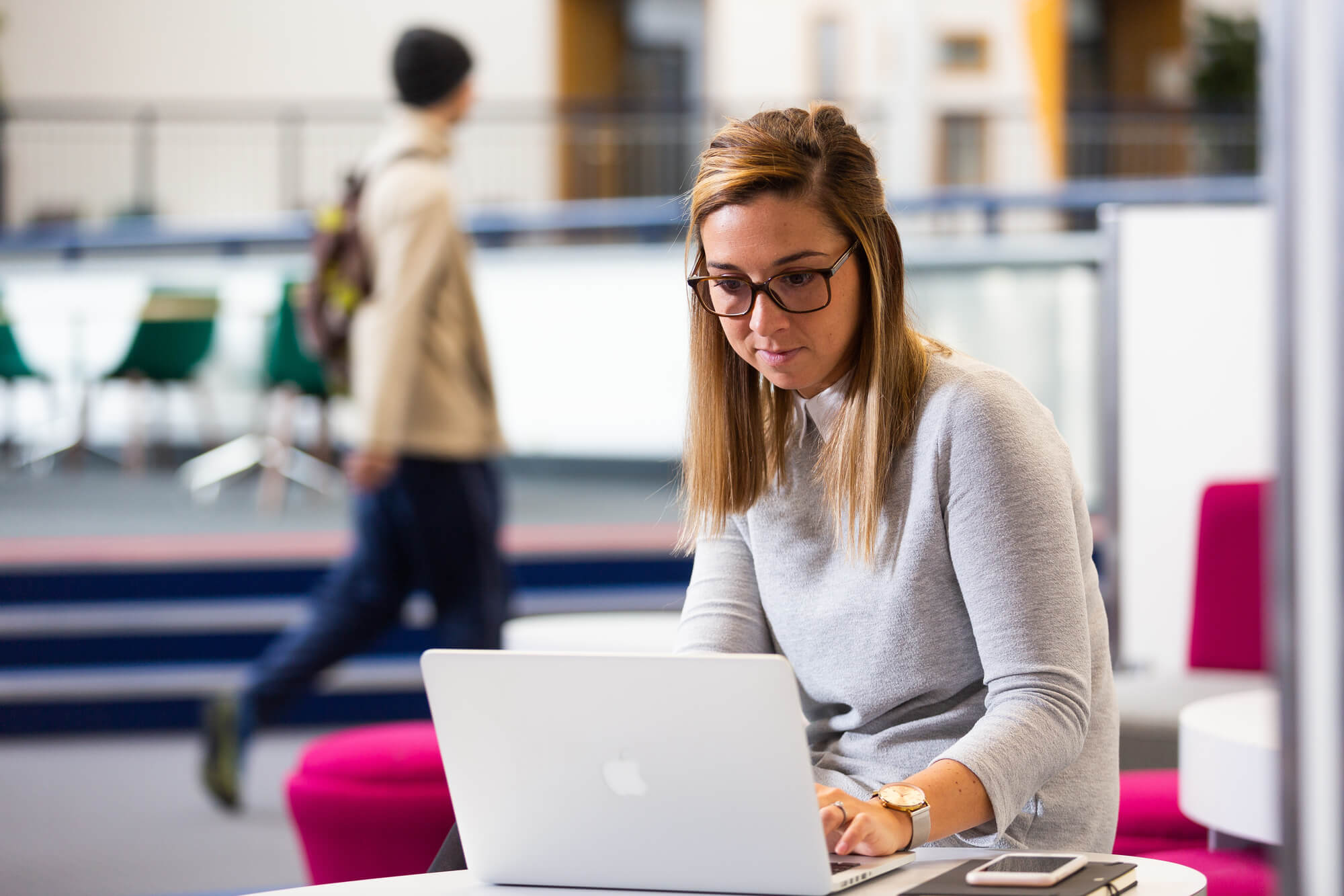 A young woman works on a macbook in the University atrium