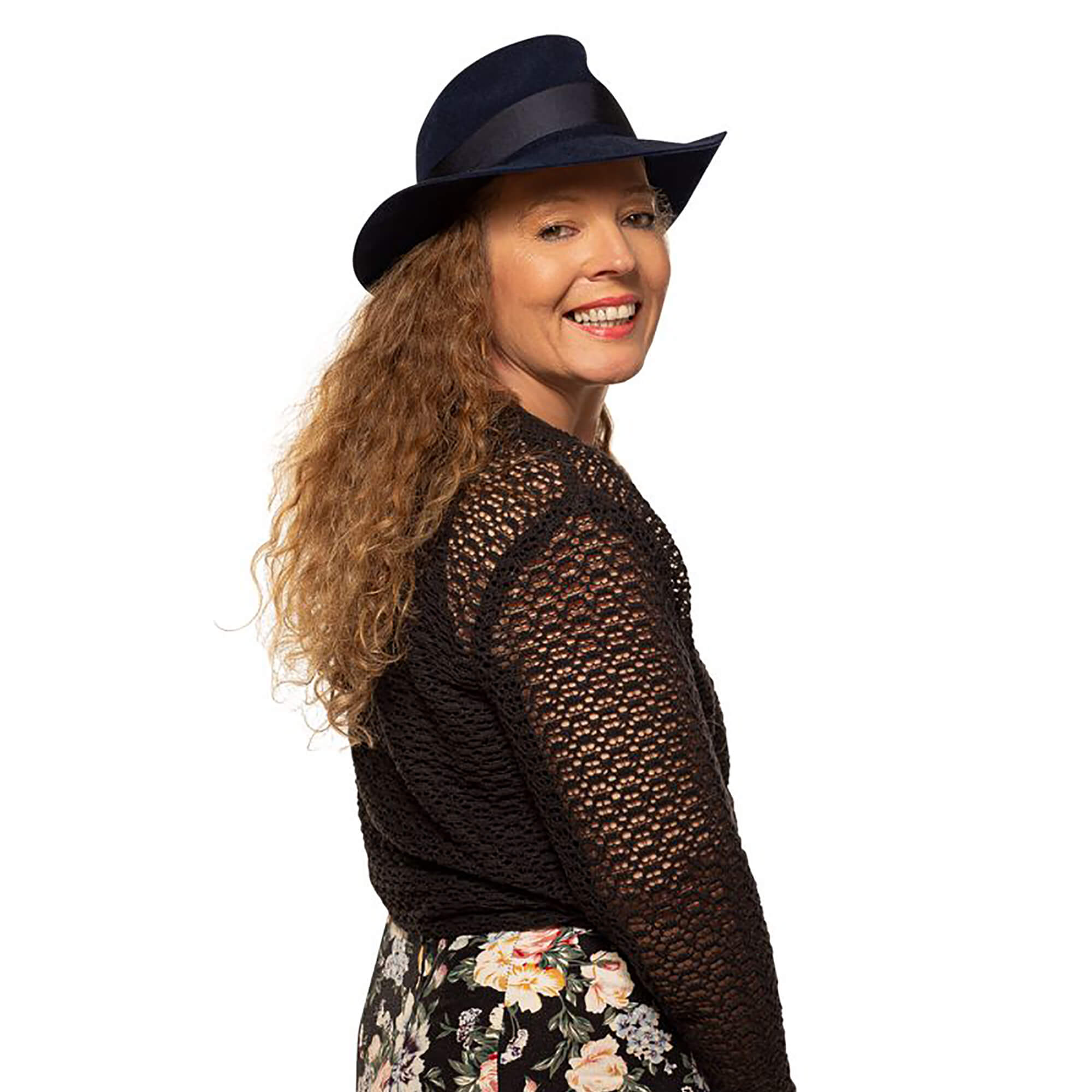 Ali standing against a white background, wearing a fedora hat, smiling.