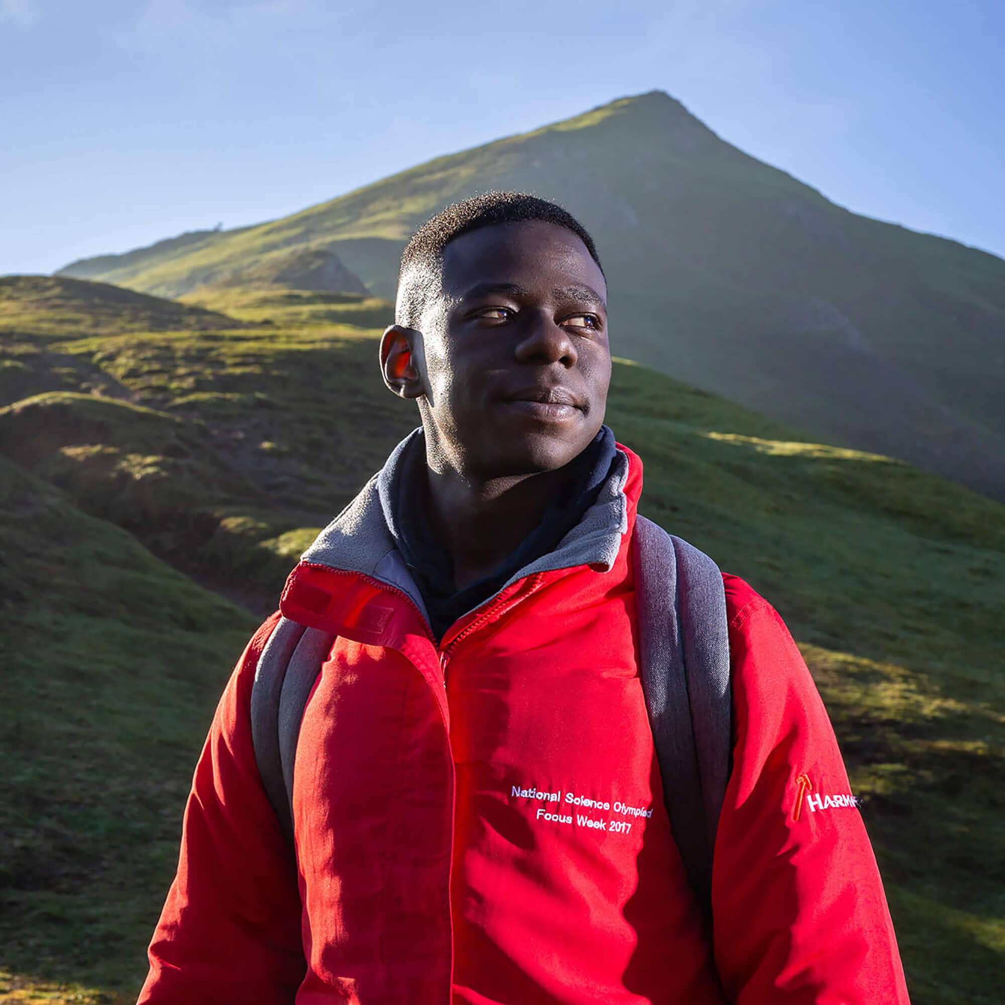 Sam standing next to a mountain wearing a red anorak.