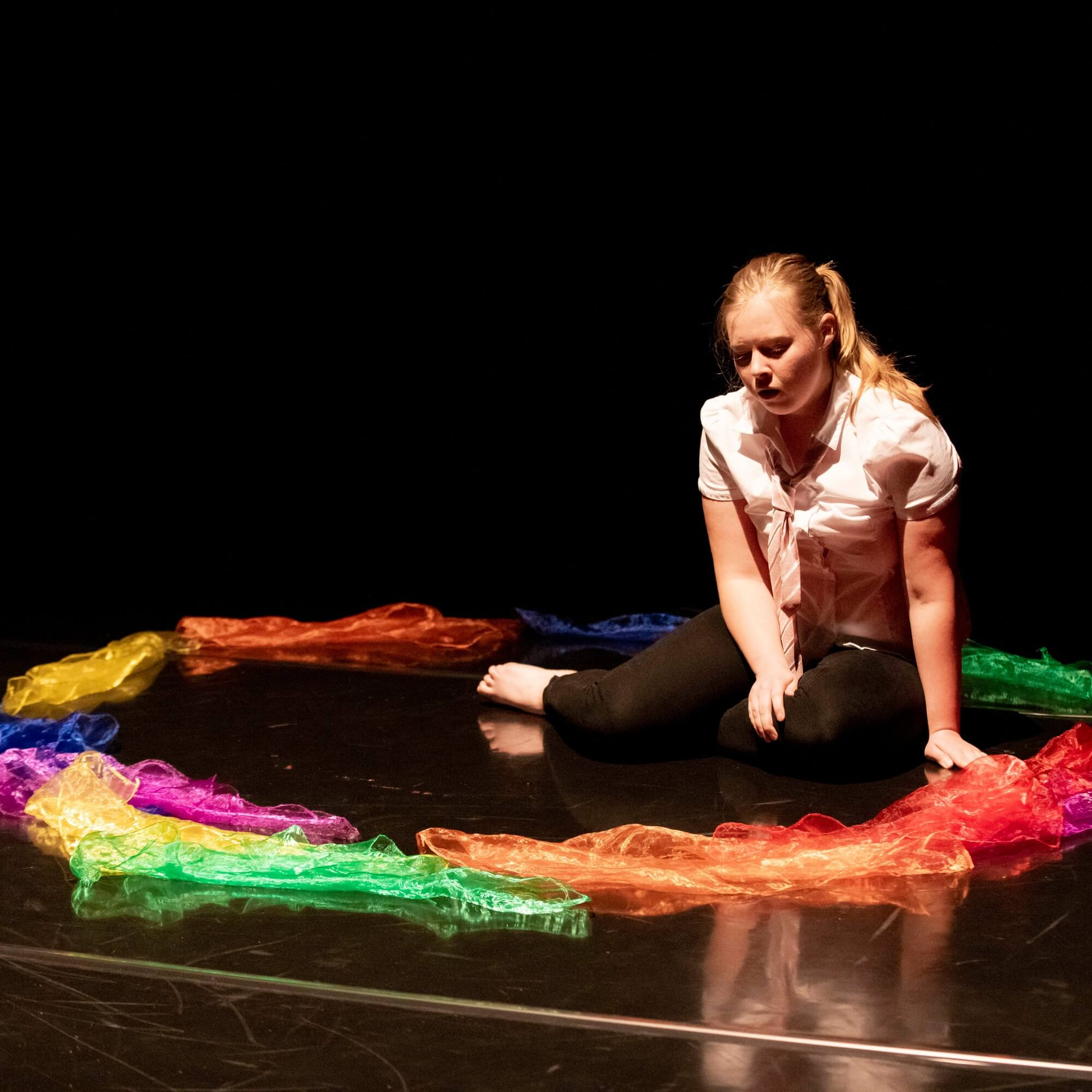 A student sitting on a theatre stage surrounded by a circle of brightly coloured handkerchiefs