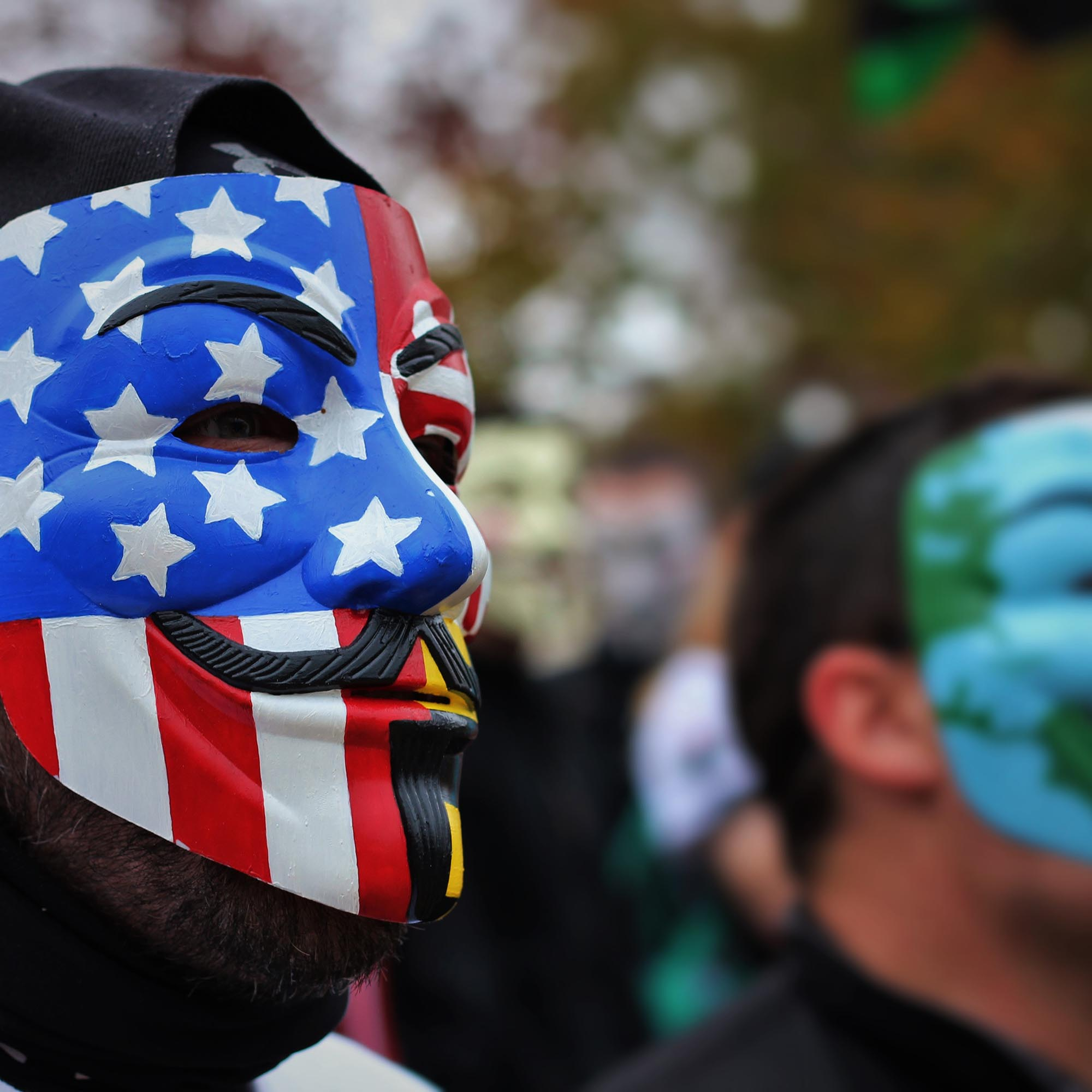 Protesters in multi-coloured Guy Fawkes masks