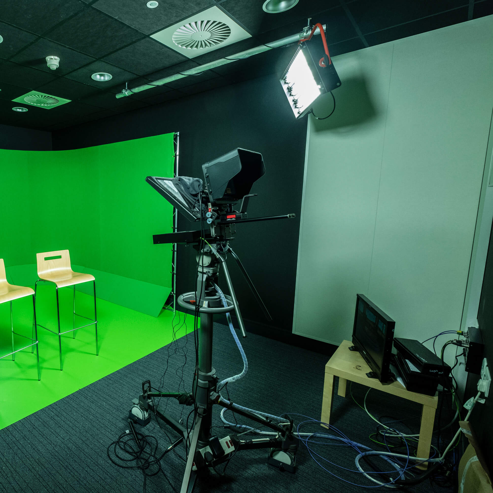 A studio with a television camera and two chairs against a green screen