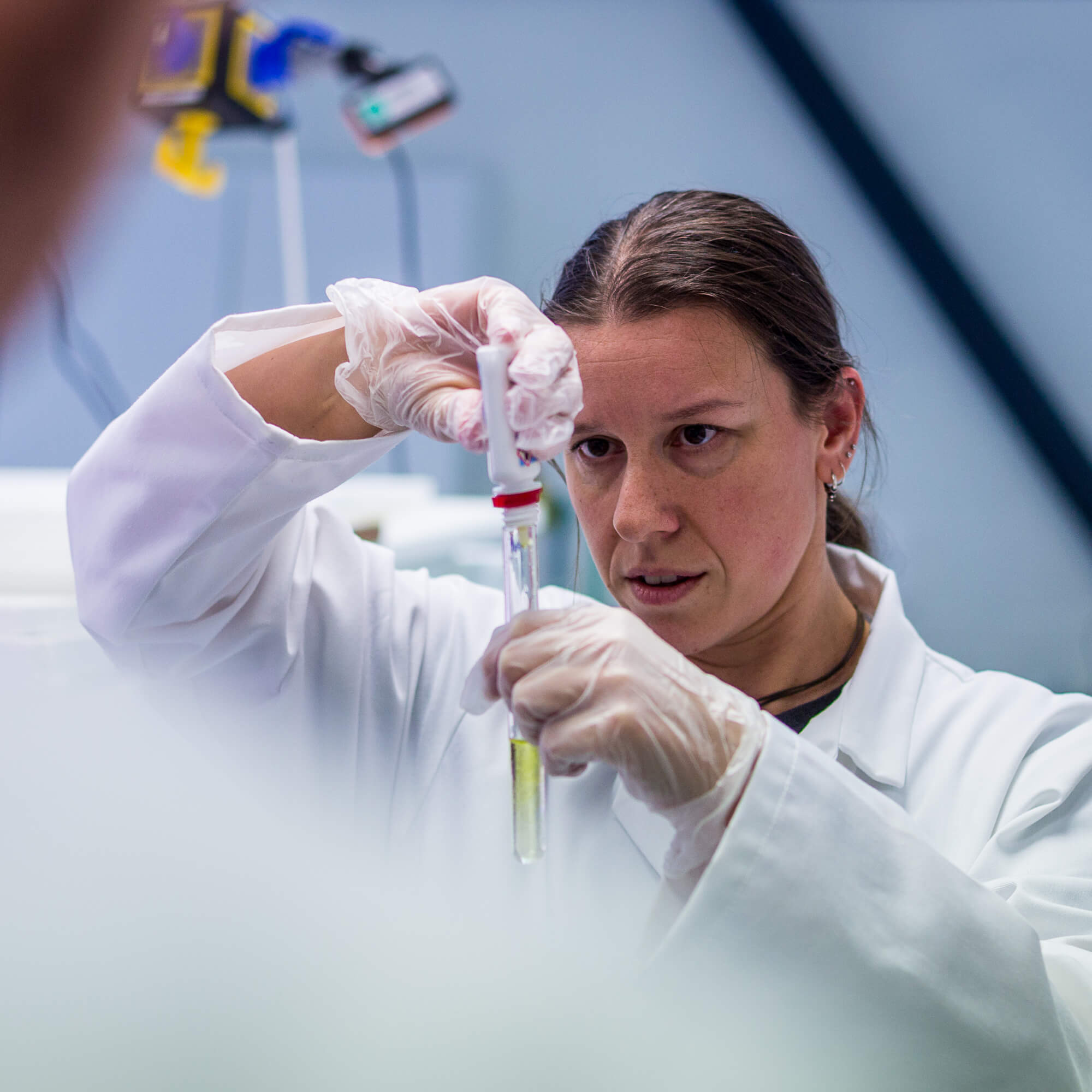 A female researcher dropping liquid into a test tube from a pipette