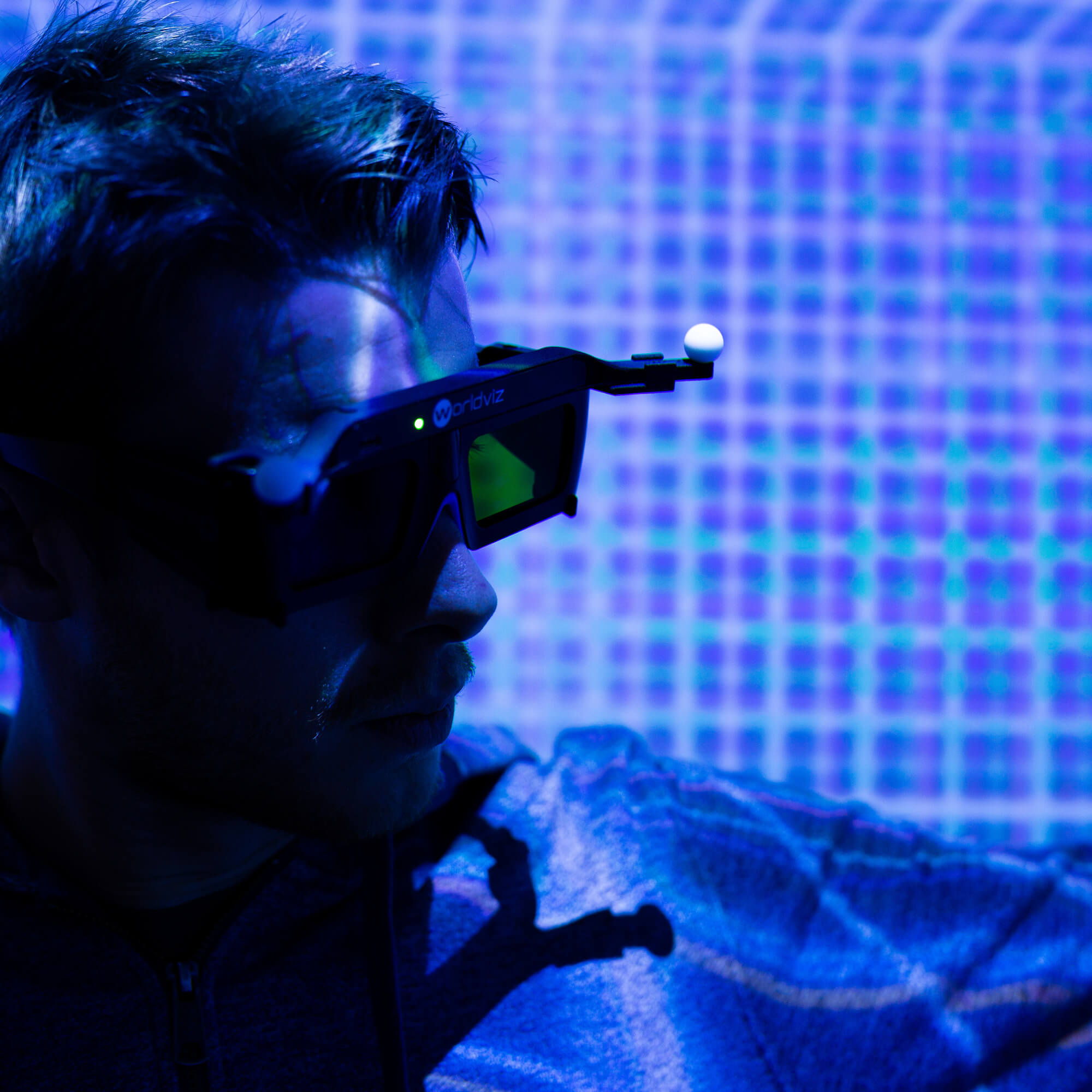 A man in a pair of augmented reality glasses in a room with a grid projected on the walls